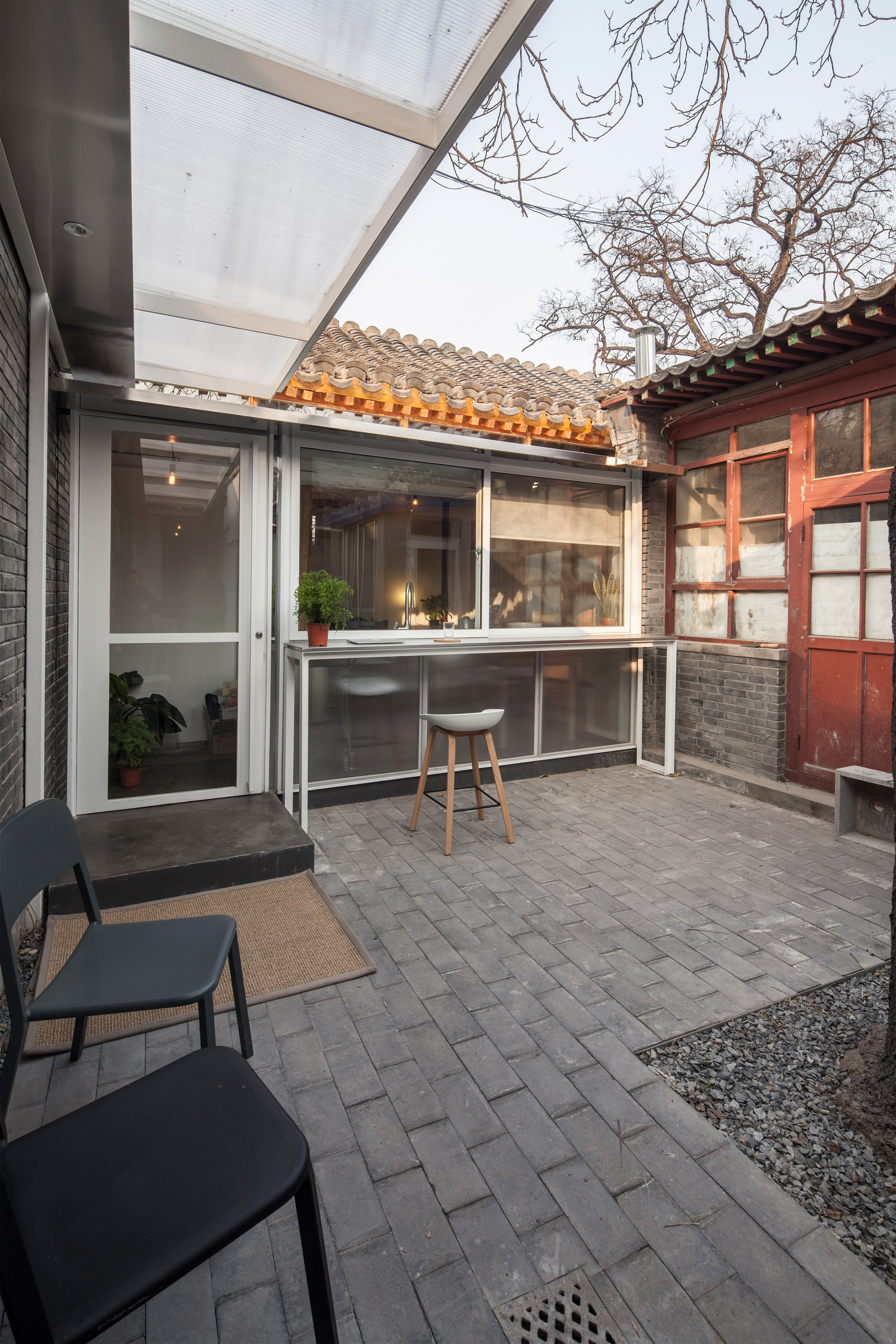 White steel extension and large windows update historic hutong home in Beijing