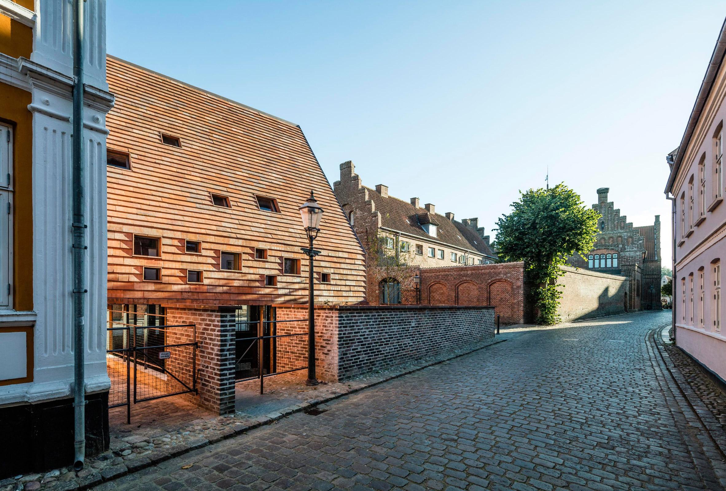 Lundgaard & Tranberg's tile-clad building shelters medieval ruins in Denmark
