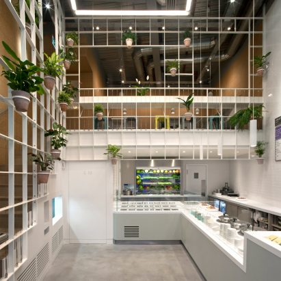 Pot plants cover trellis-like walls inside London cafe by Neiheiser Argyros