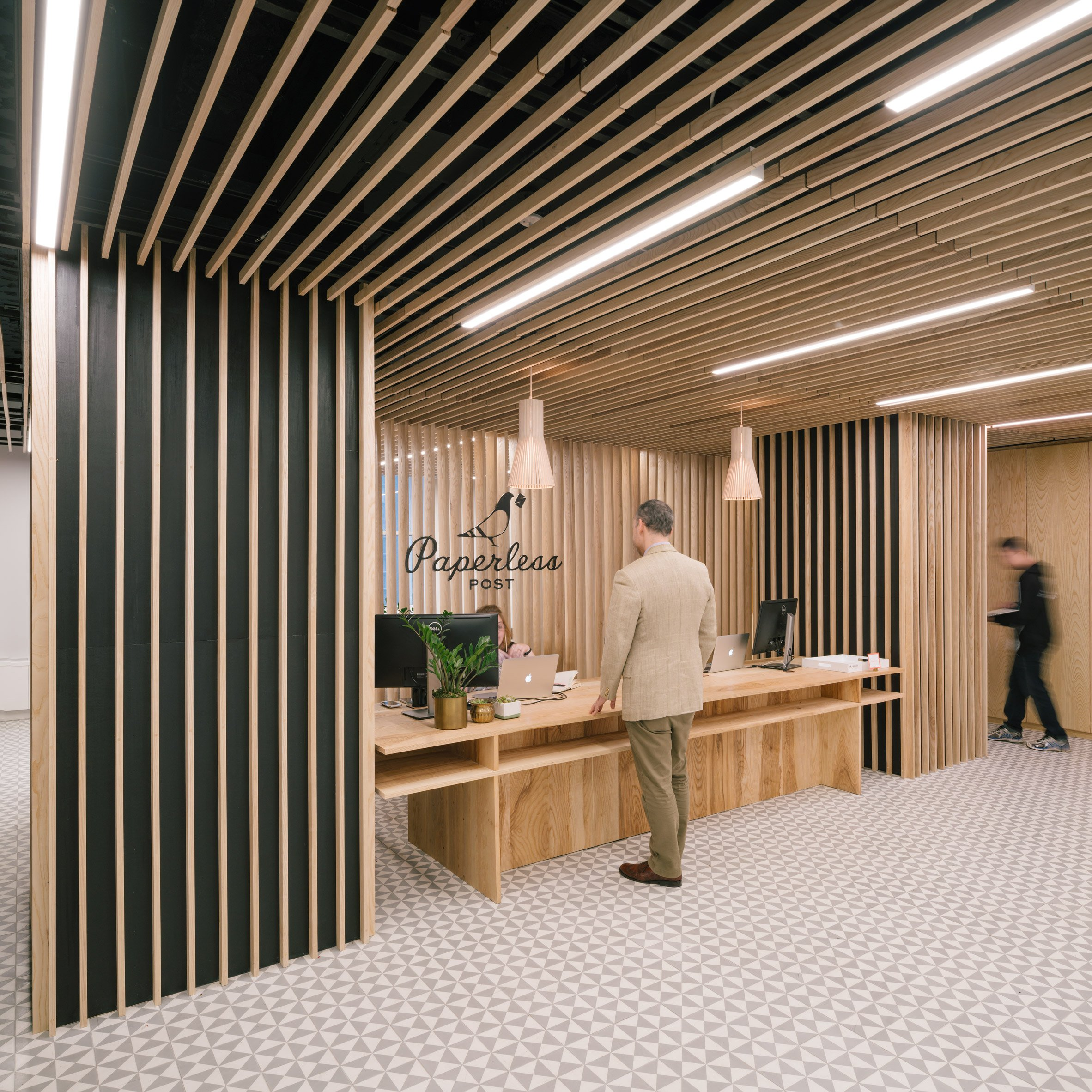 Wooden slats surround reception at Paperless Post's Manhattan offices by +ADD