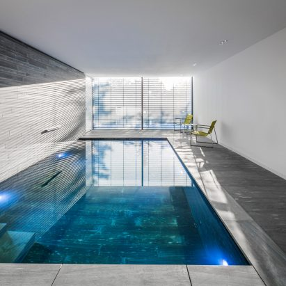 stone lined swimming pool in cologne house features large window with garden views - Design A Swimming Pool
