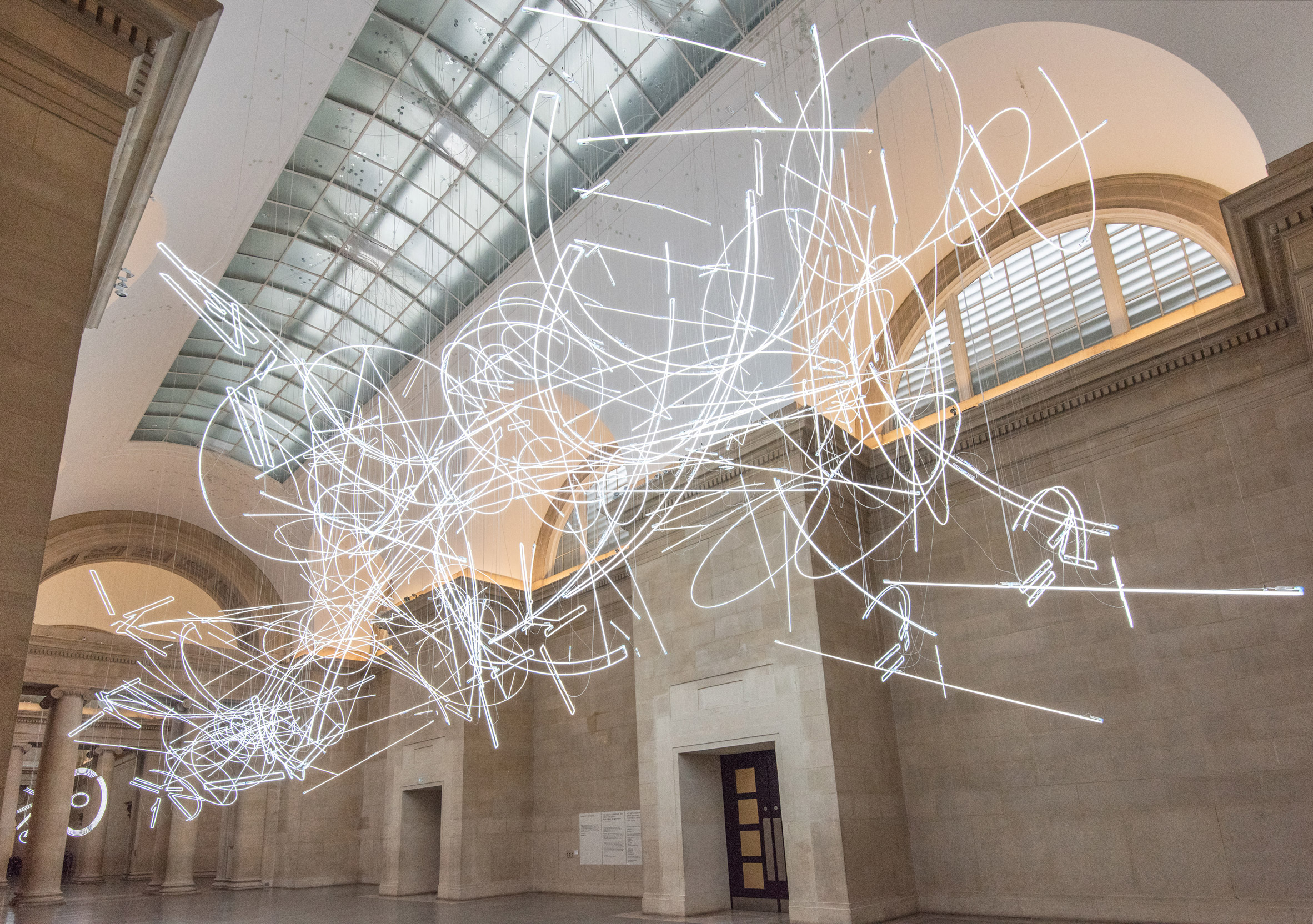 Neon scribbles by Cerith Wyn Evans hang in London's Tate Britain