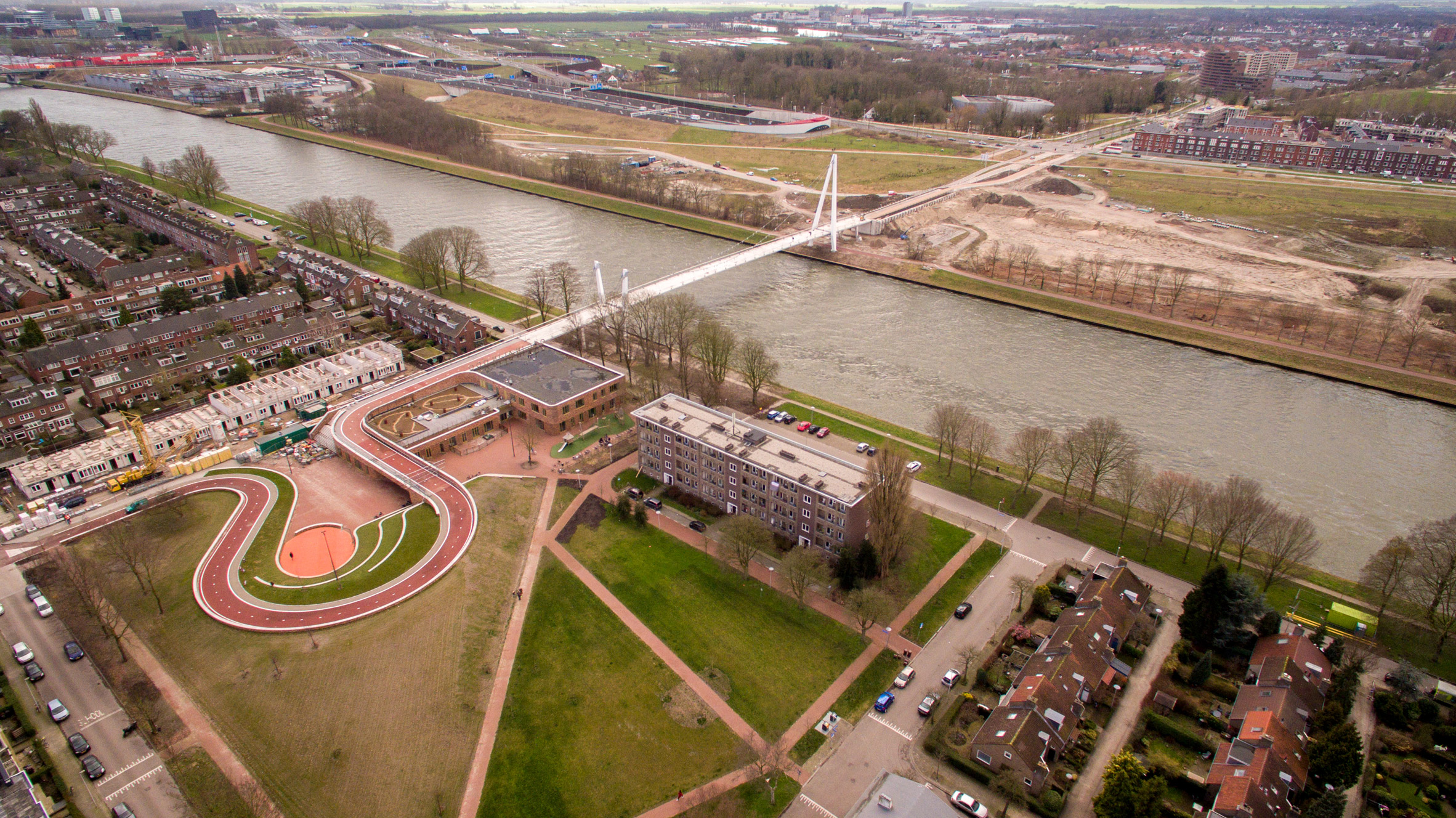 Red cycle path by NEXT and Rudy Uytenhaak snakes over Utrecht school and canal