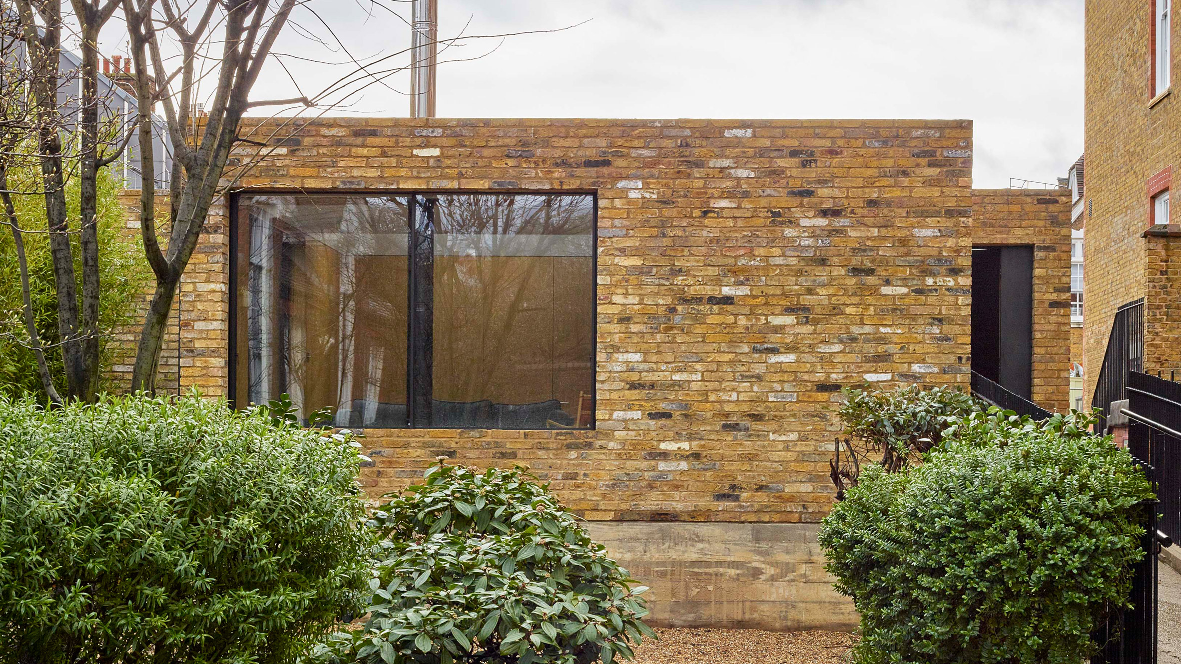 Coffey Architects sets small brick home atop Victorian