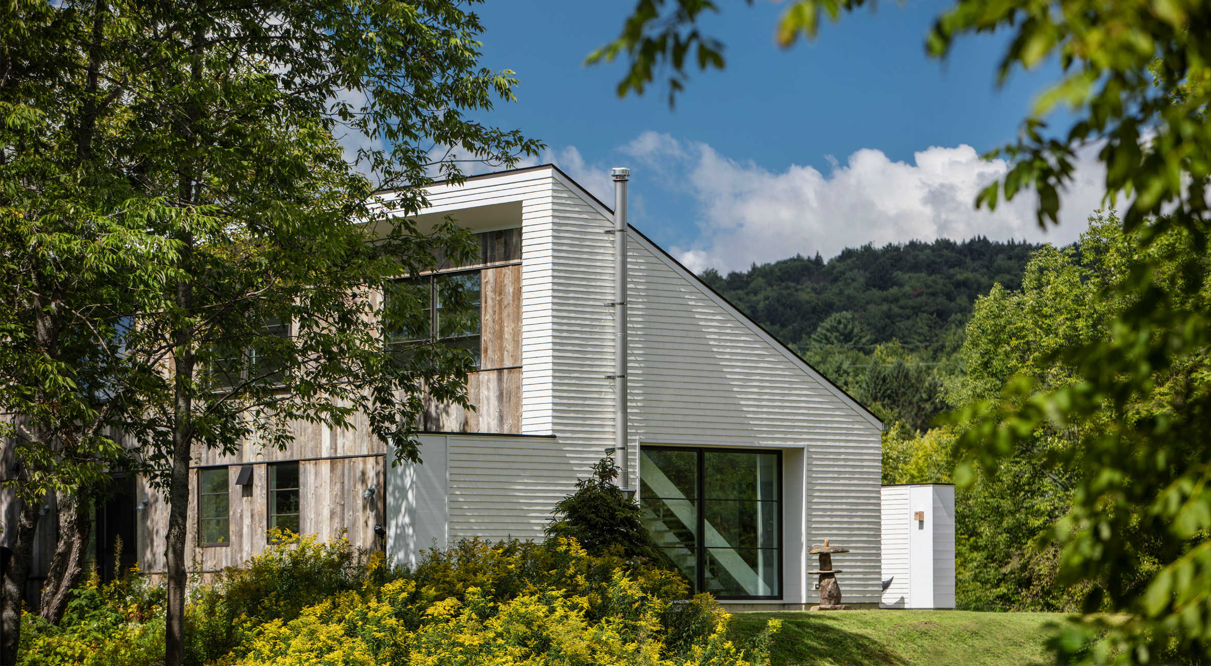 Two white volumes frame central courtyard of Vermont home by Birdseye Design