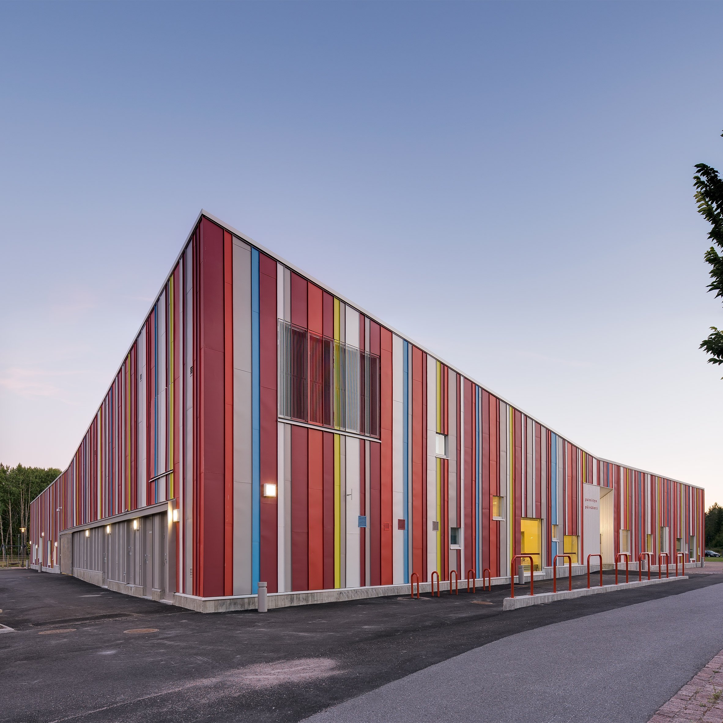 AFKS wraps horseshoe-shaped kindergarten in stripy multicoloured metal cladding