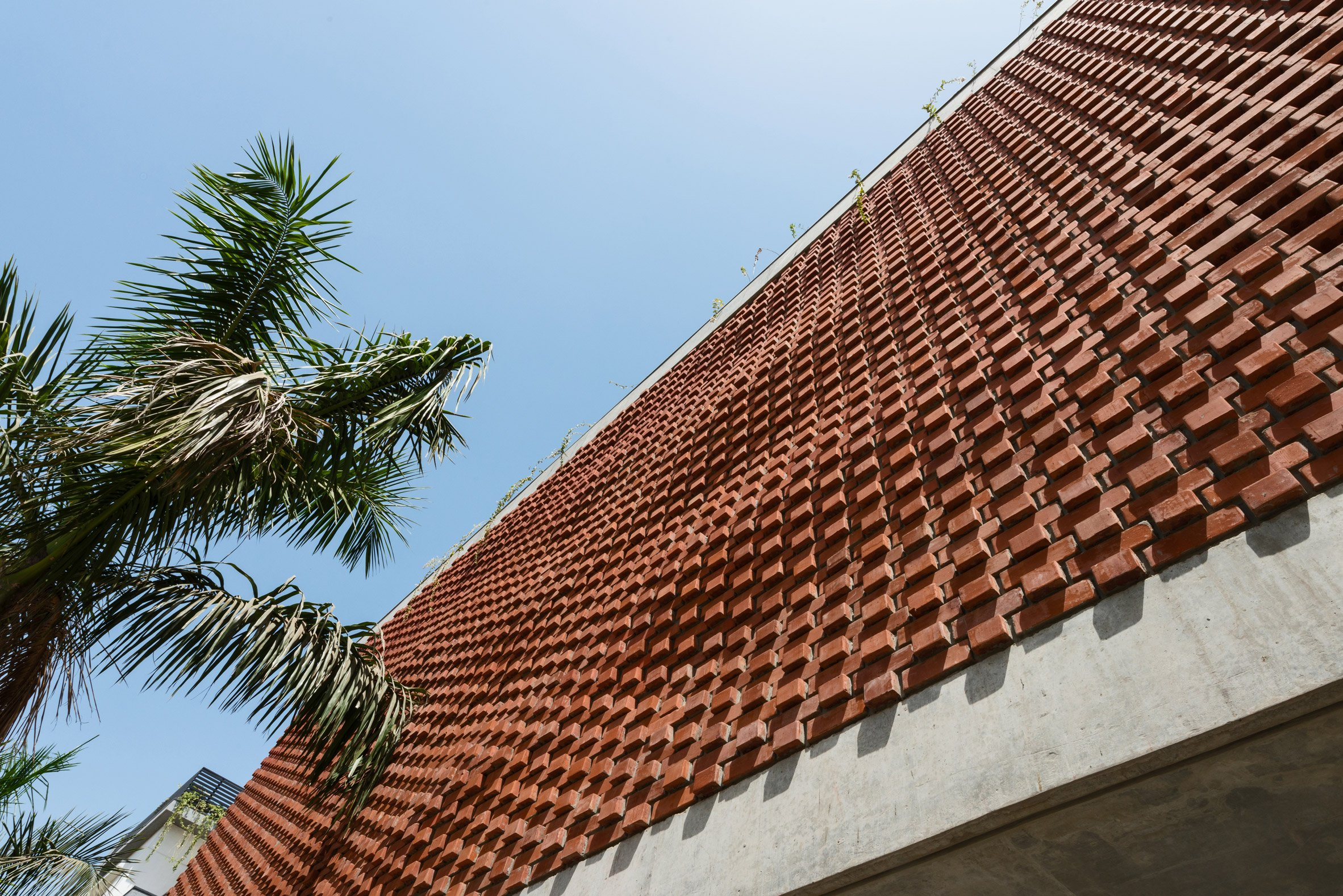 Rippling red brick facade shades house in Surat by Design Work...