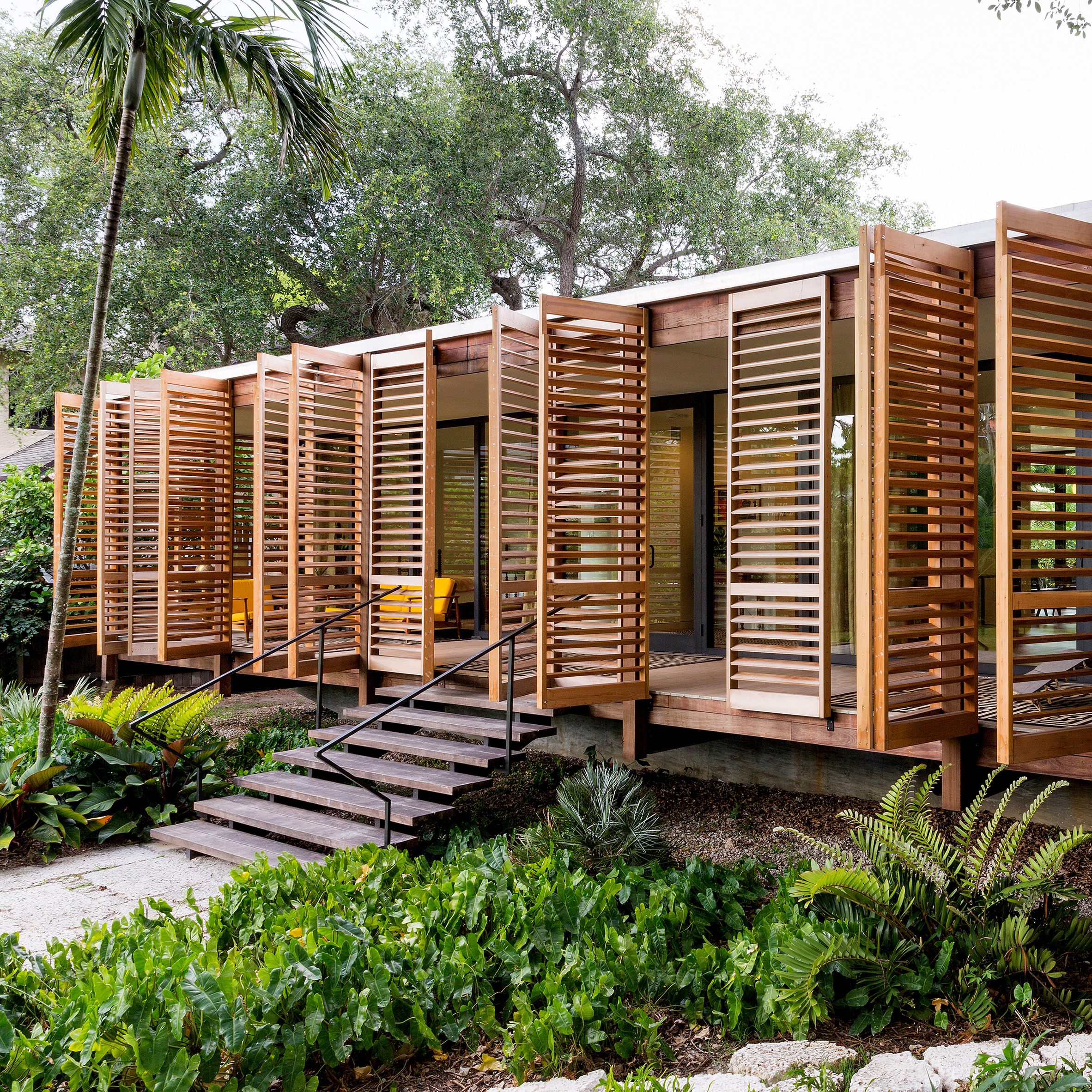 Wooden shutters open to reveal Miami house by Brillhart