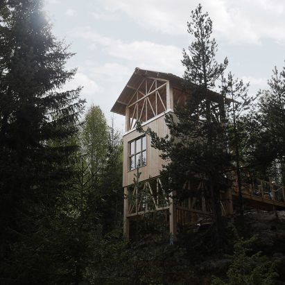 cabin by hanna michelson stands on stilts to peep over the treetops of swedish mountain