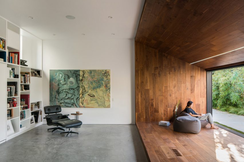 Walnut reading nook and white bookshelf in Frank Gehry house
