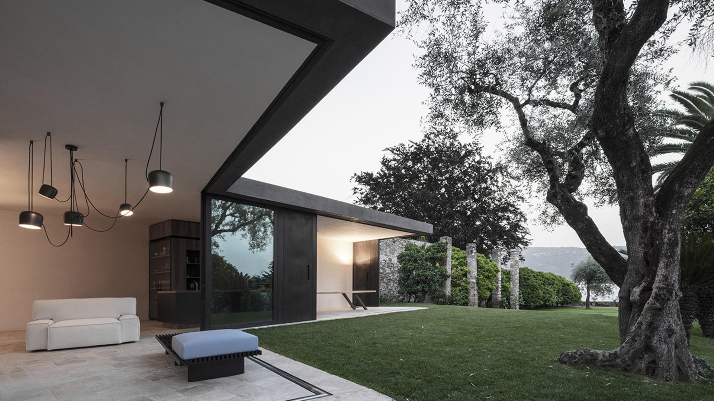 Vertically sliding walls open Italian villa extension to the garden