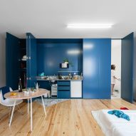 Deep-blue shutters conceal kitchens, windows and wardrobes in Porto flats by Fala Atelier