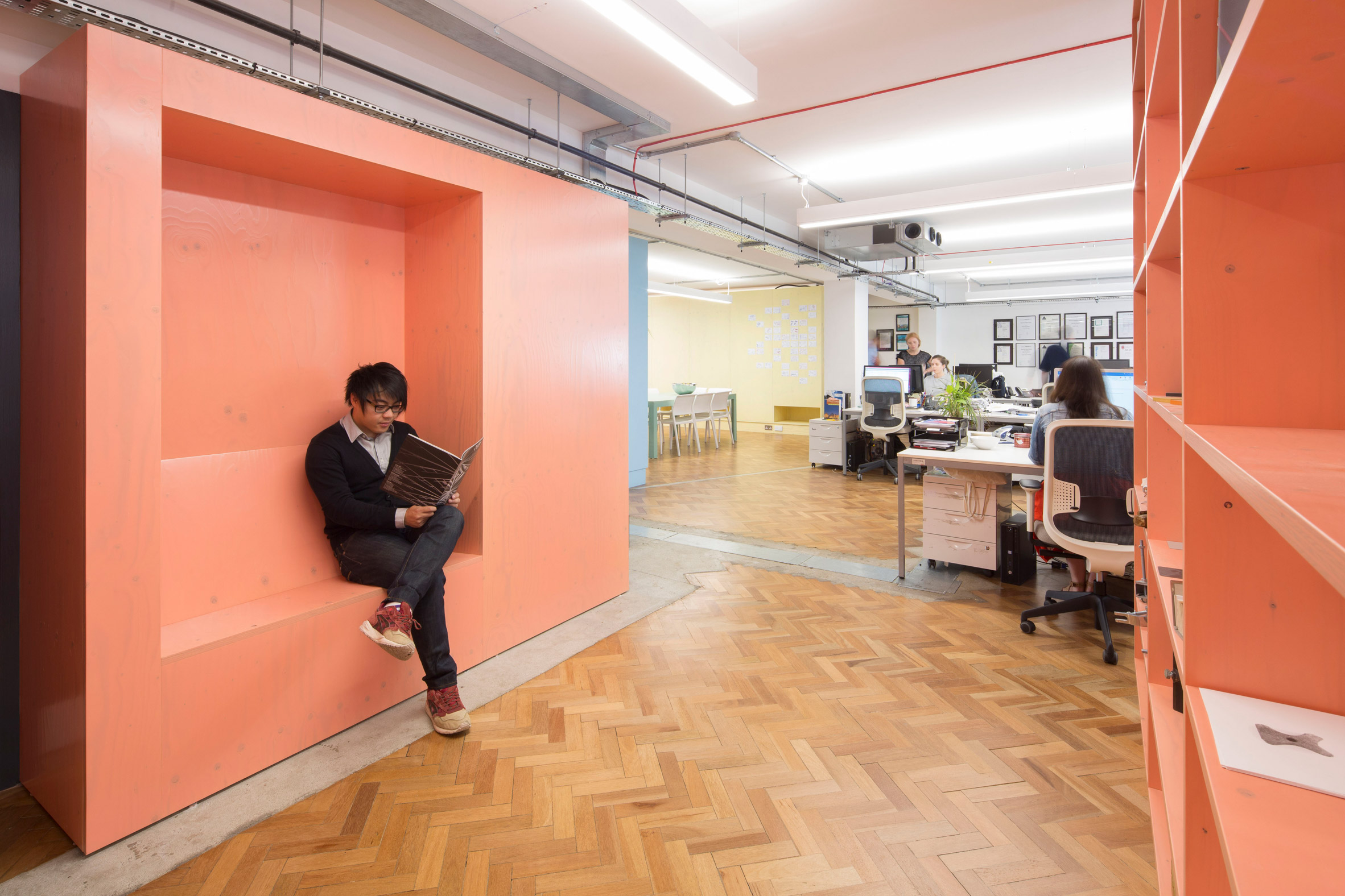 Interrobang fills its office with custom plywood furniture painted the colours of insulating foam