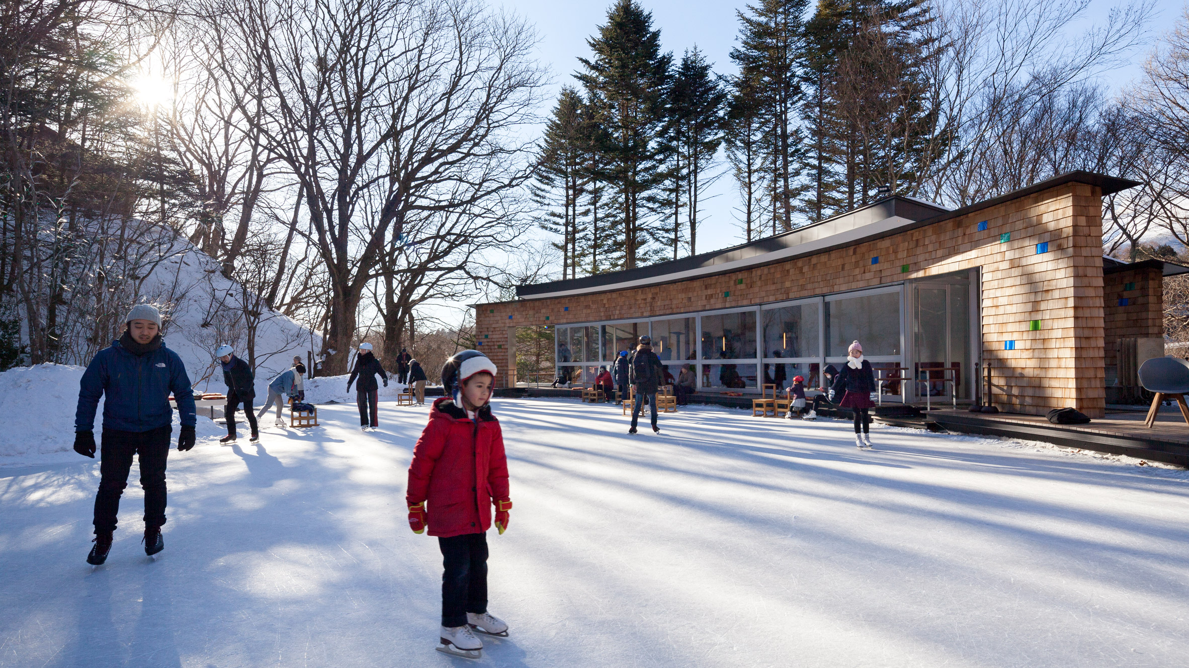 shingled clubhouse and visitor centre faces ice rink in a japanese