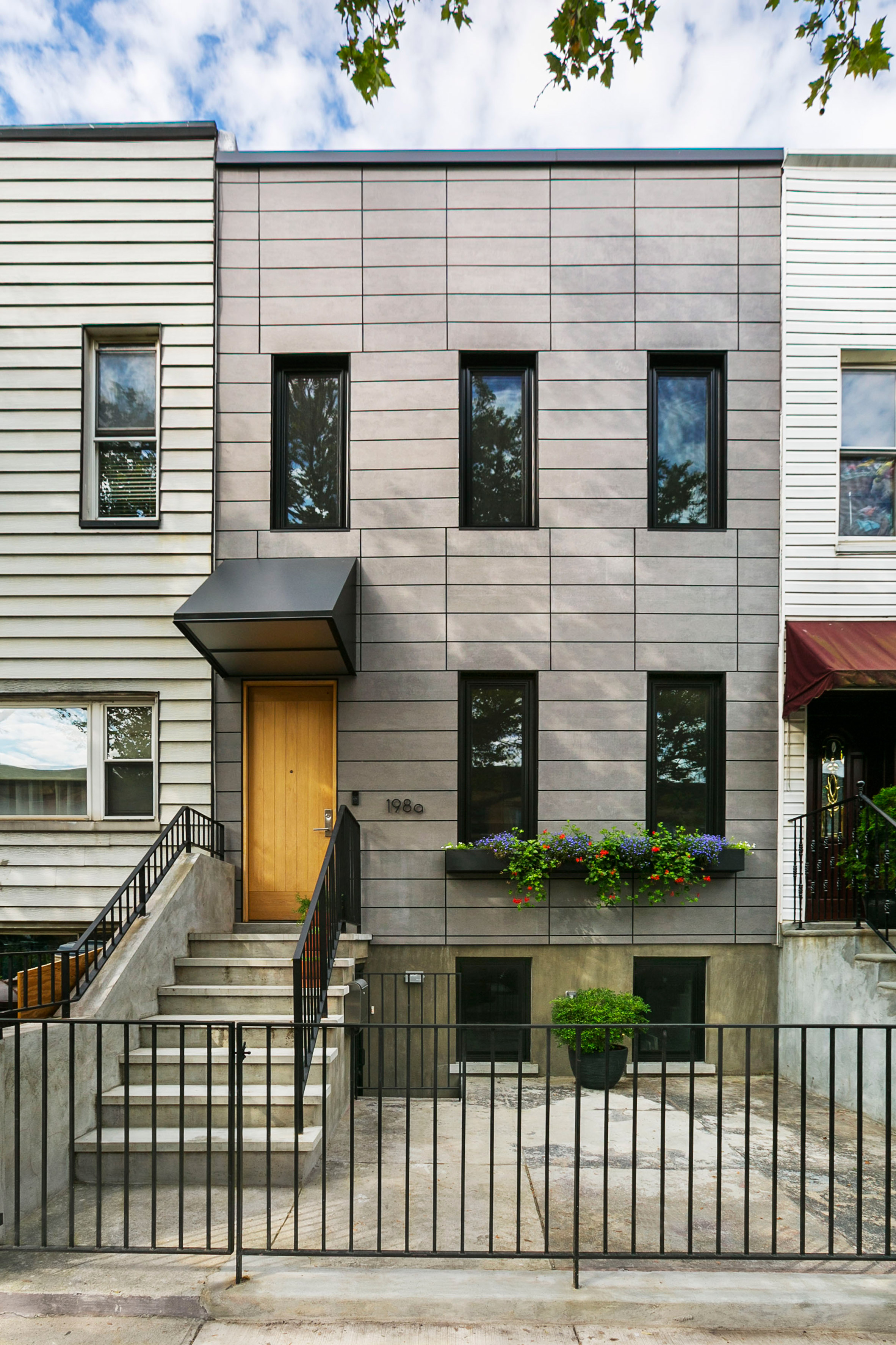 Bostudio updates Sunset Park Row House with fibre-cement cladding and open layout