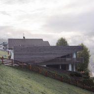 Plasma Studio's copper-clad apartment block has huge windows facing the Dolomites