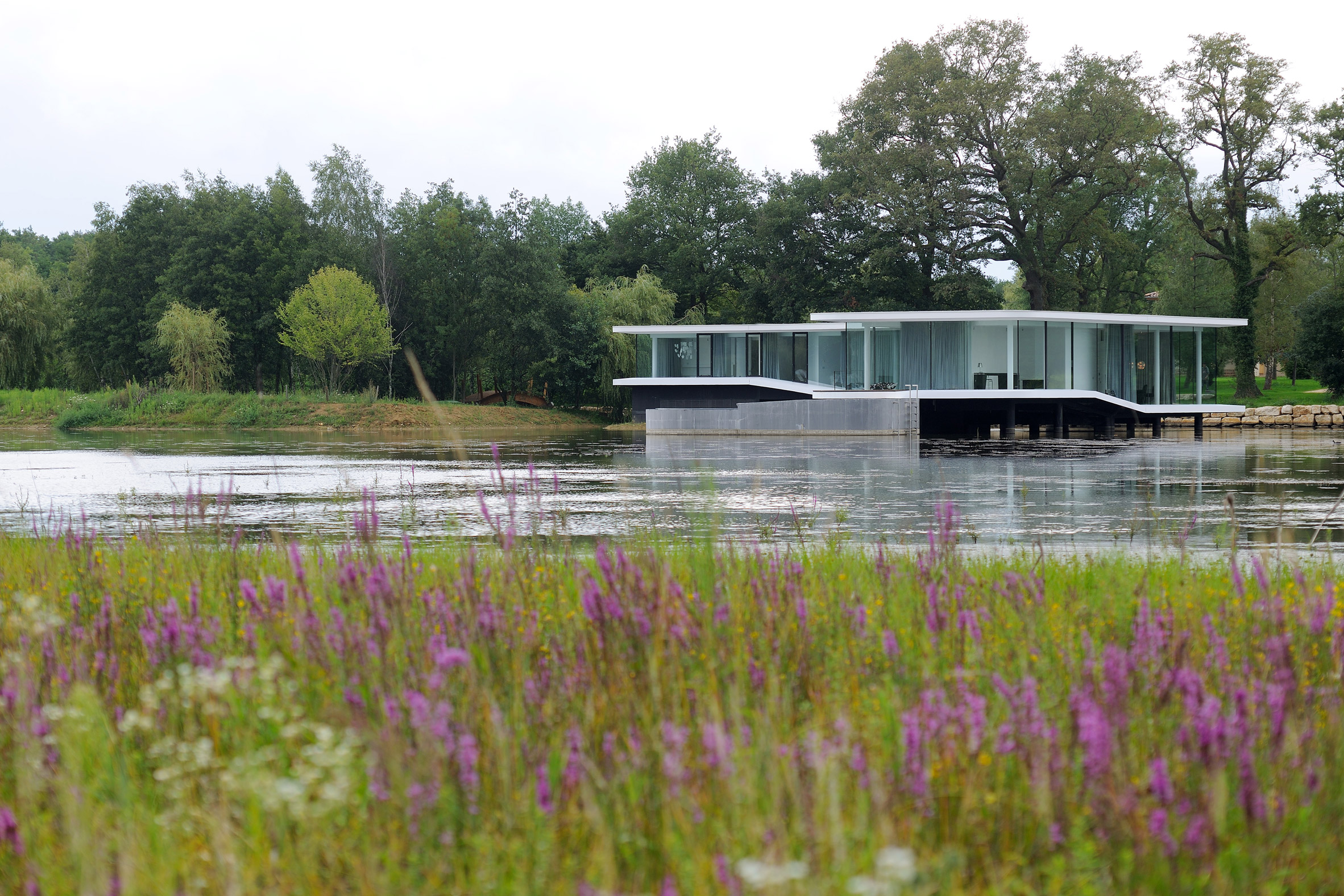 AUM builds curving concrete and glass residence on the surface of a lake