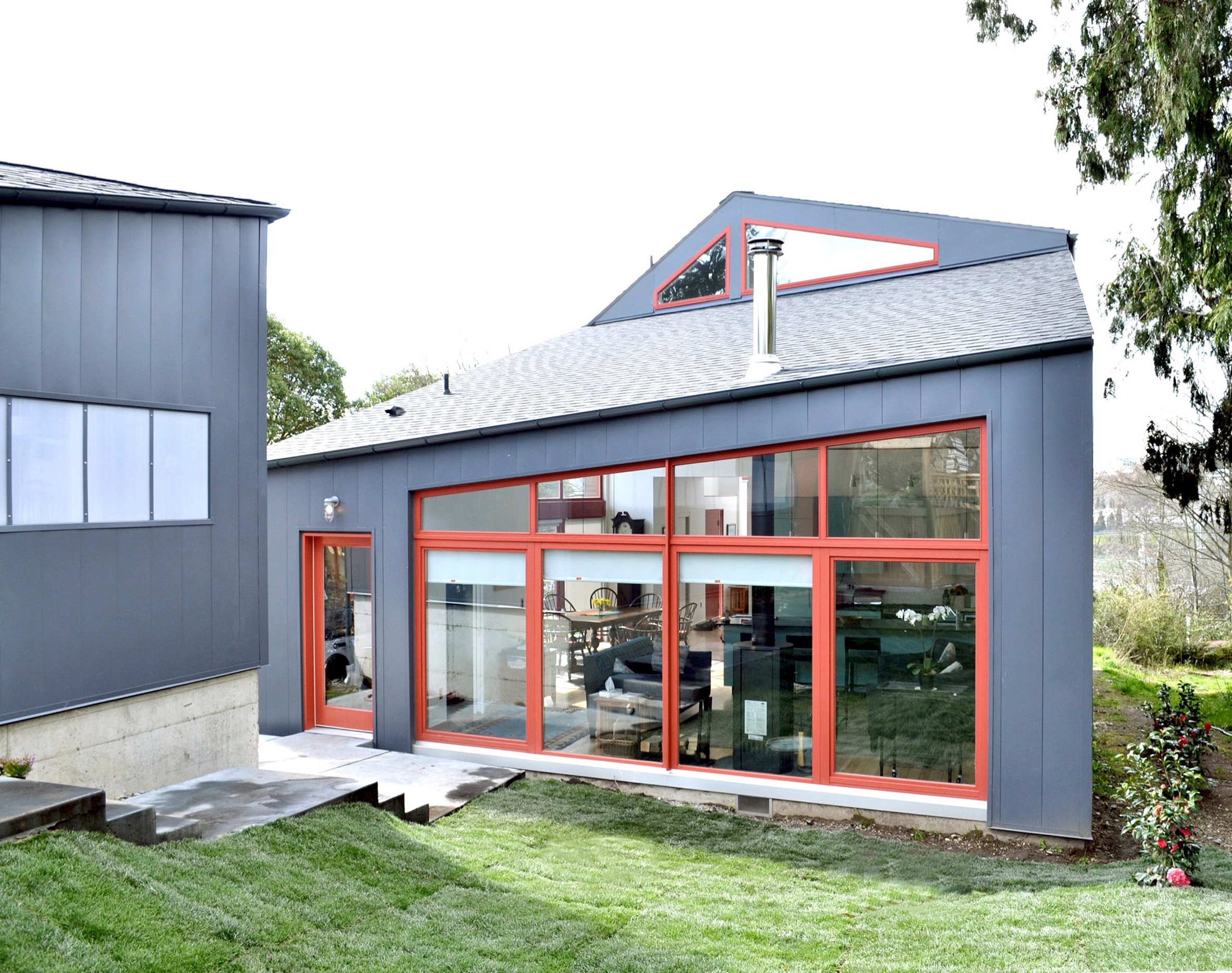 Red window frames accent angular Seattle house by Stettler Design