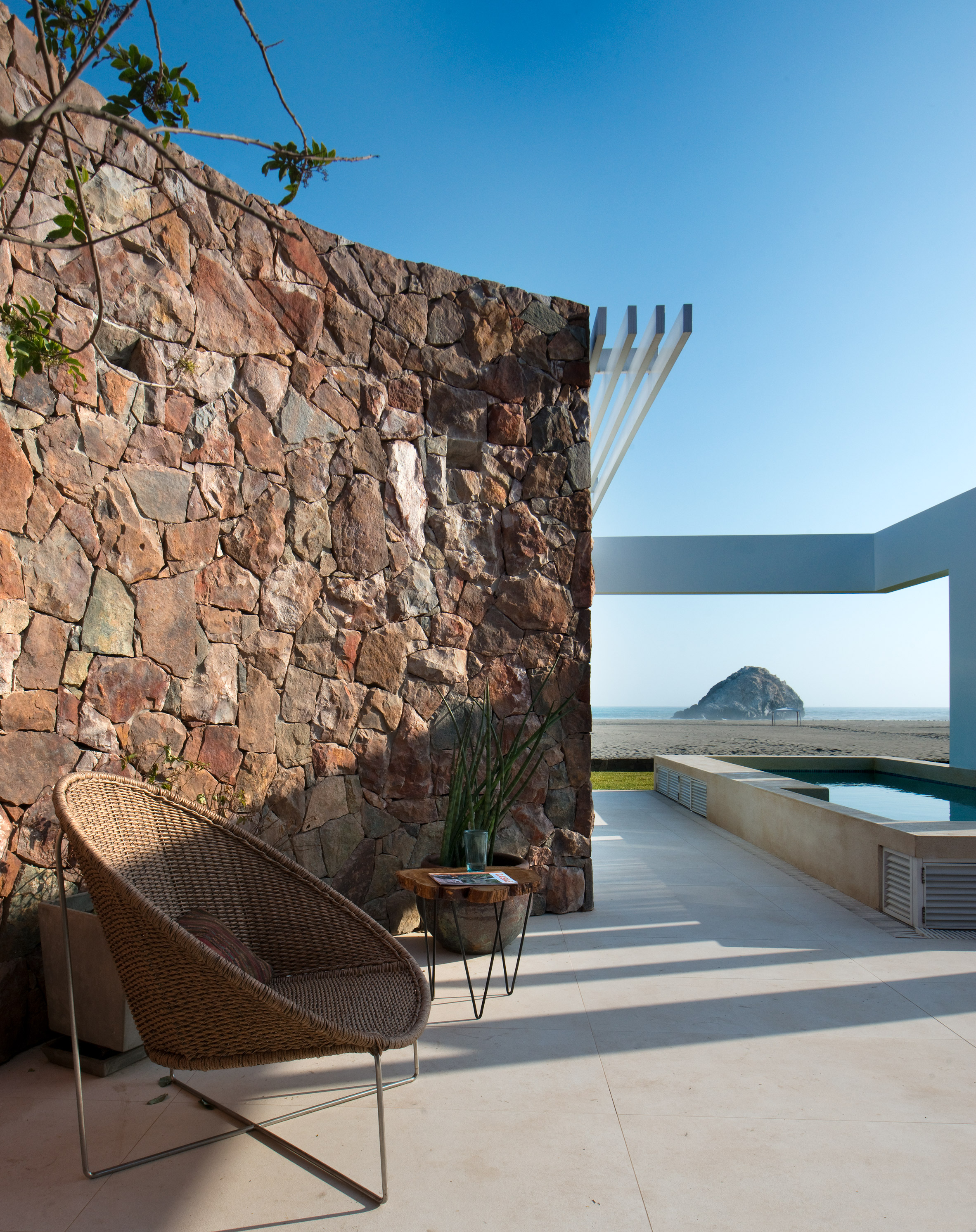 Mountain rubble forms curving wall inside coastal Peru house by Marina Vella