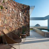Mountain rubble forms curving wall inside coastal Peru house by Marina Vella