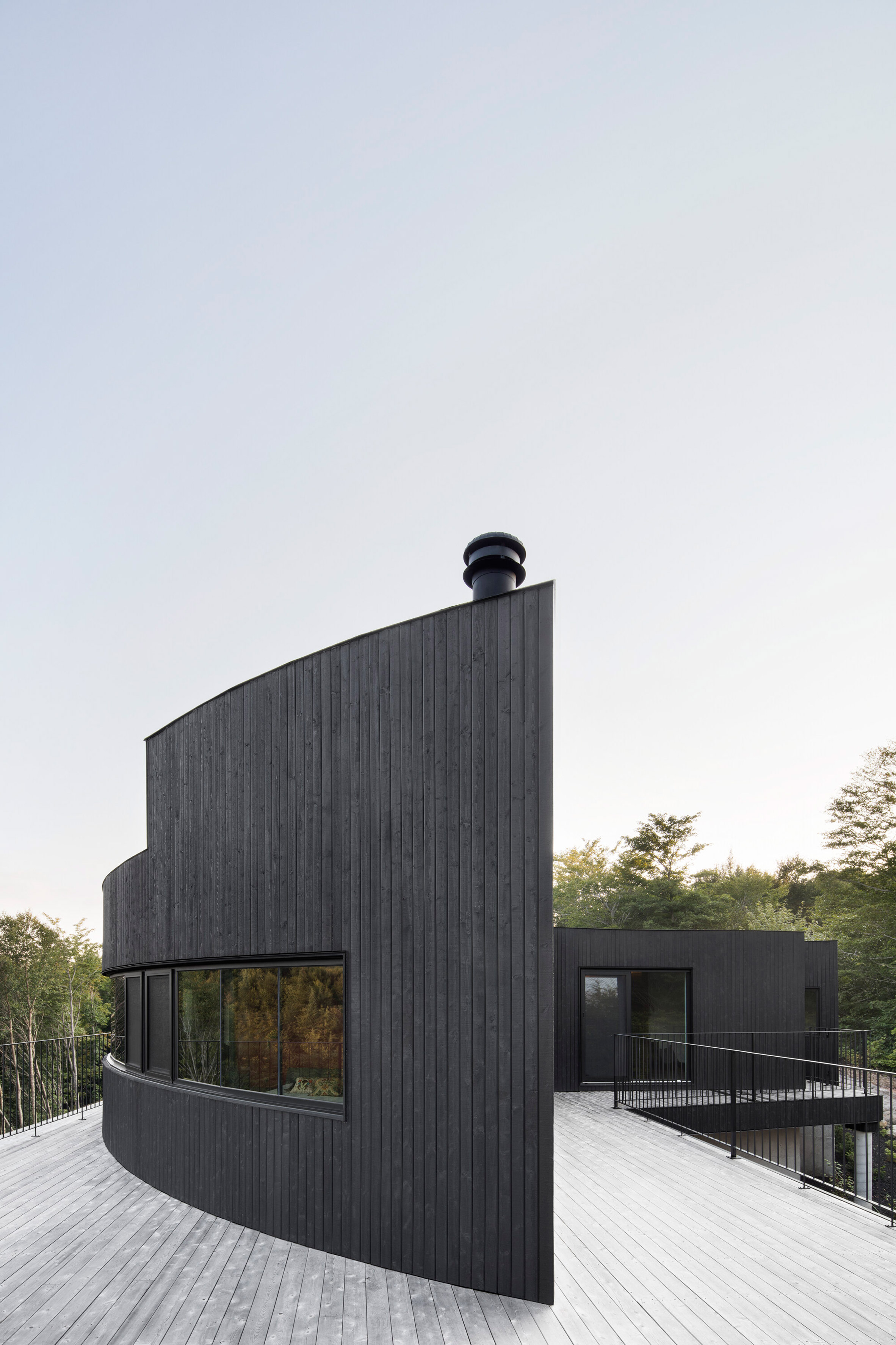 Expansive deck divides levels of Canadian cliffside house by Alain Carle