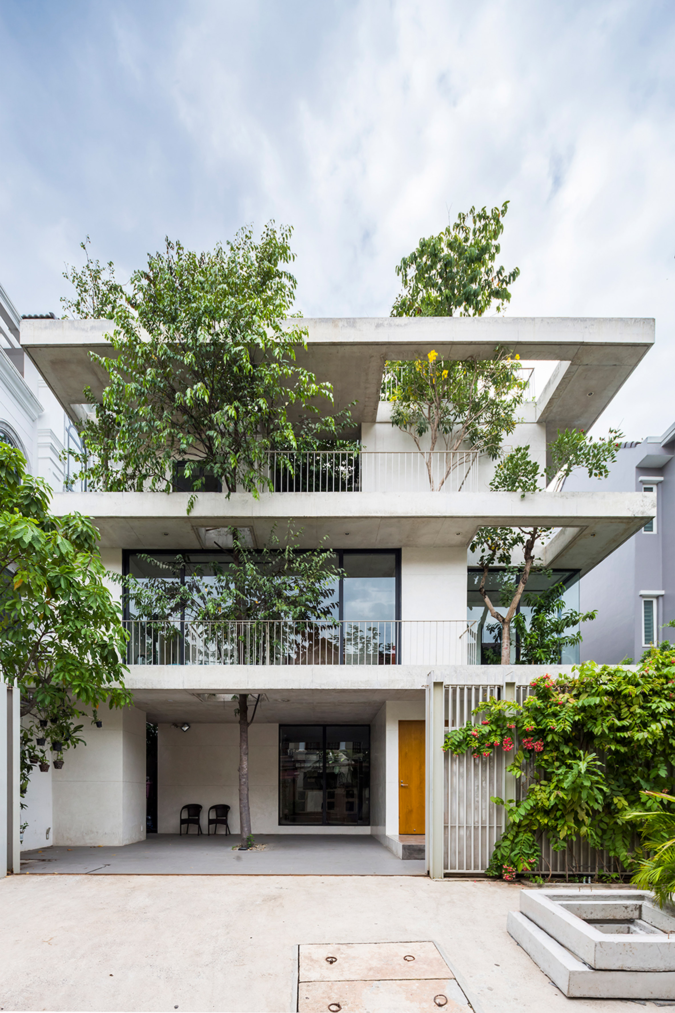 Tree branches poke through floors of Vo Trong Nghia's Stacked Planters House