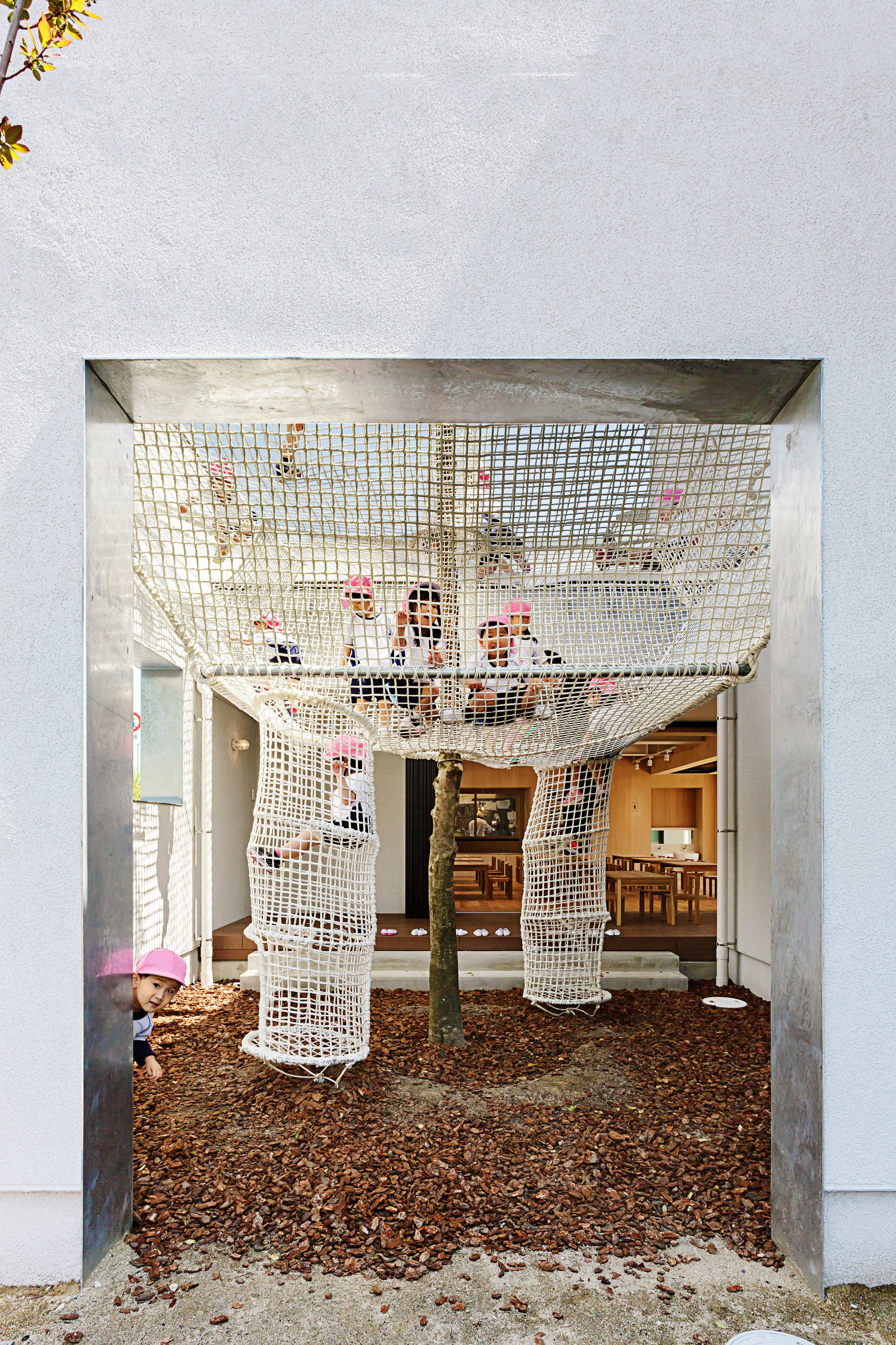 Climbing nets surround tree extending through balcony of for Balcony surrounds