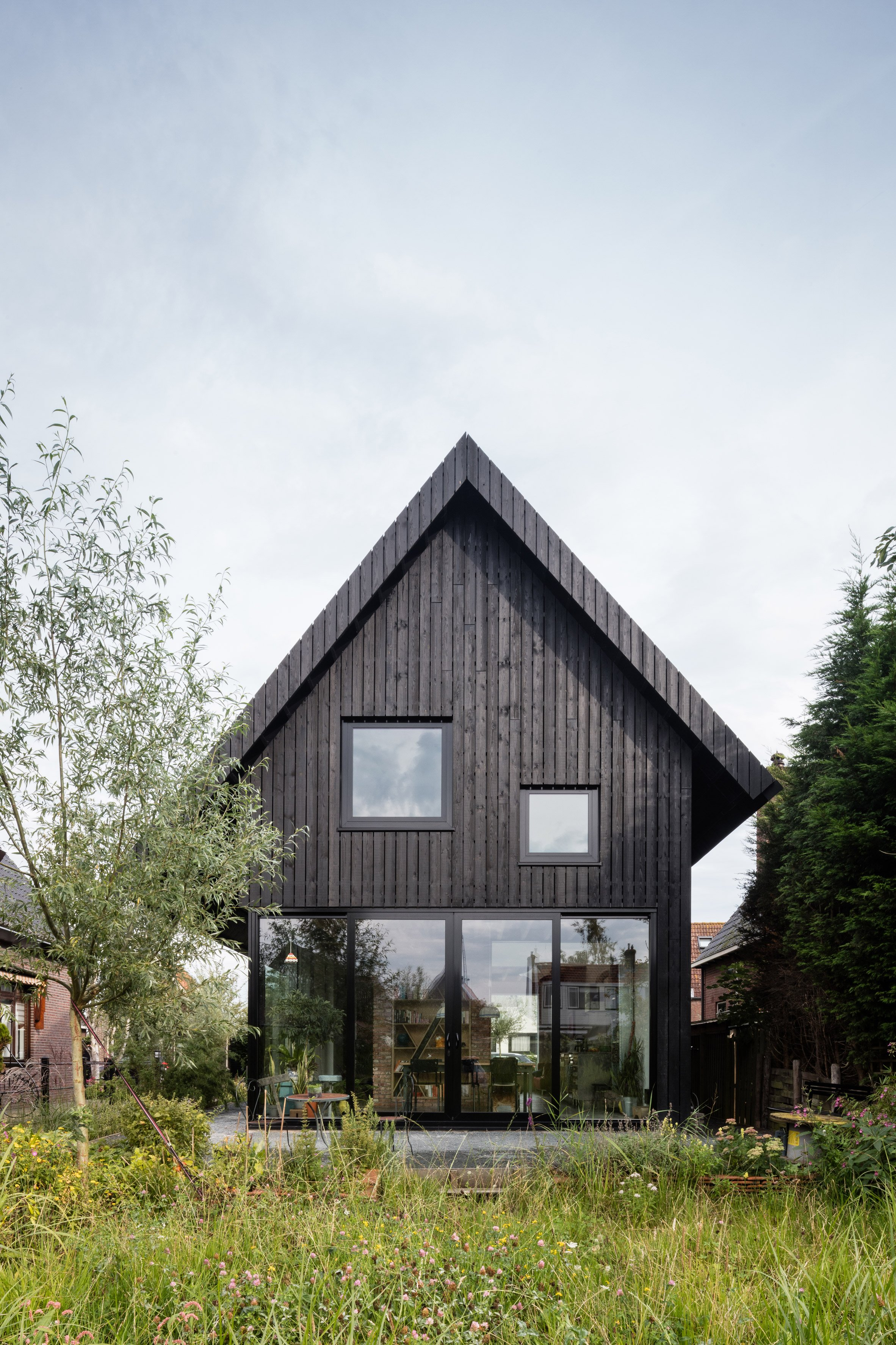 Chris Collaris Architects completes black wooden cottage with exaggerated roof