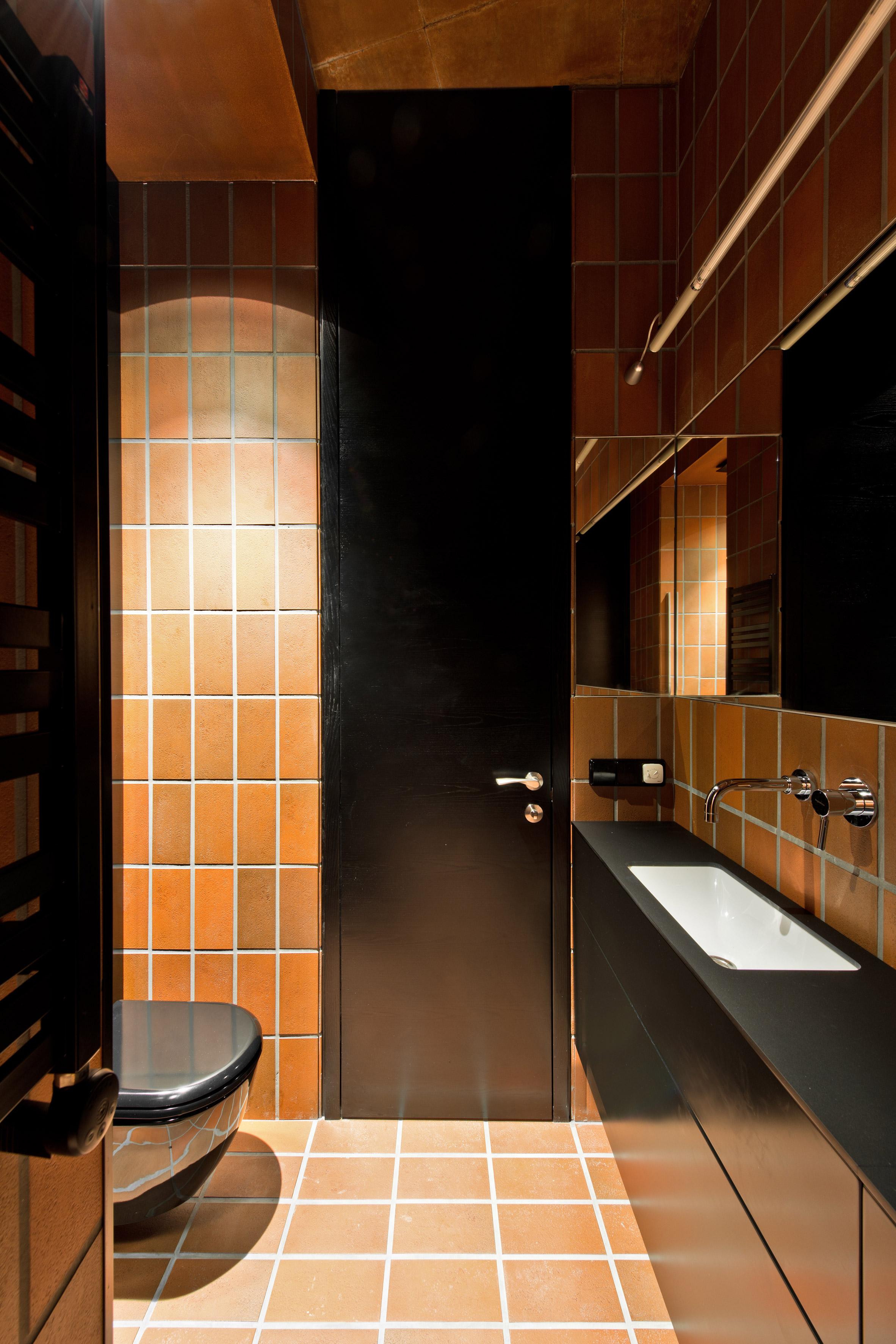 terracotta toned tiles divide vilnius apartment into two agrob buchtal goldline tiles in bazillion apartment by - Terra Cotta Tile Apartment 2015