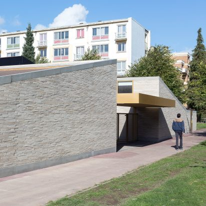 LT2A's brick school extension features porthole-like screens and gold-hued surfaces
