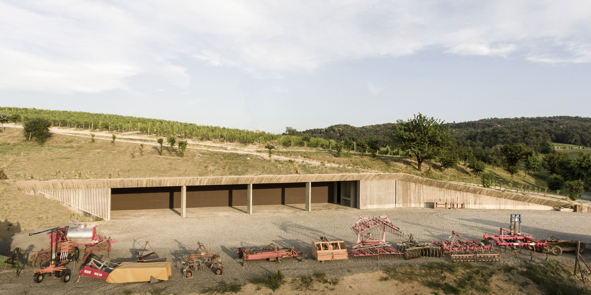 Concrete machinery depot by Deamicisarchitetti is submerged in a hillside at La Raia estate