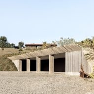 Concrete machinery depot by Deamicisarchitetti is submerged in a hillside