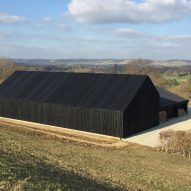Black-stained barn built by Macdonald Wright Architects at Caring Wood country house