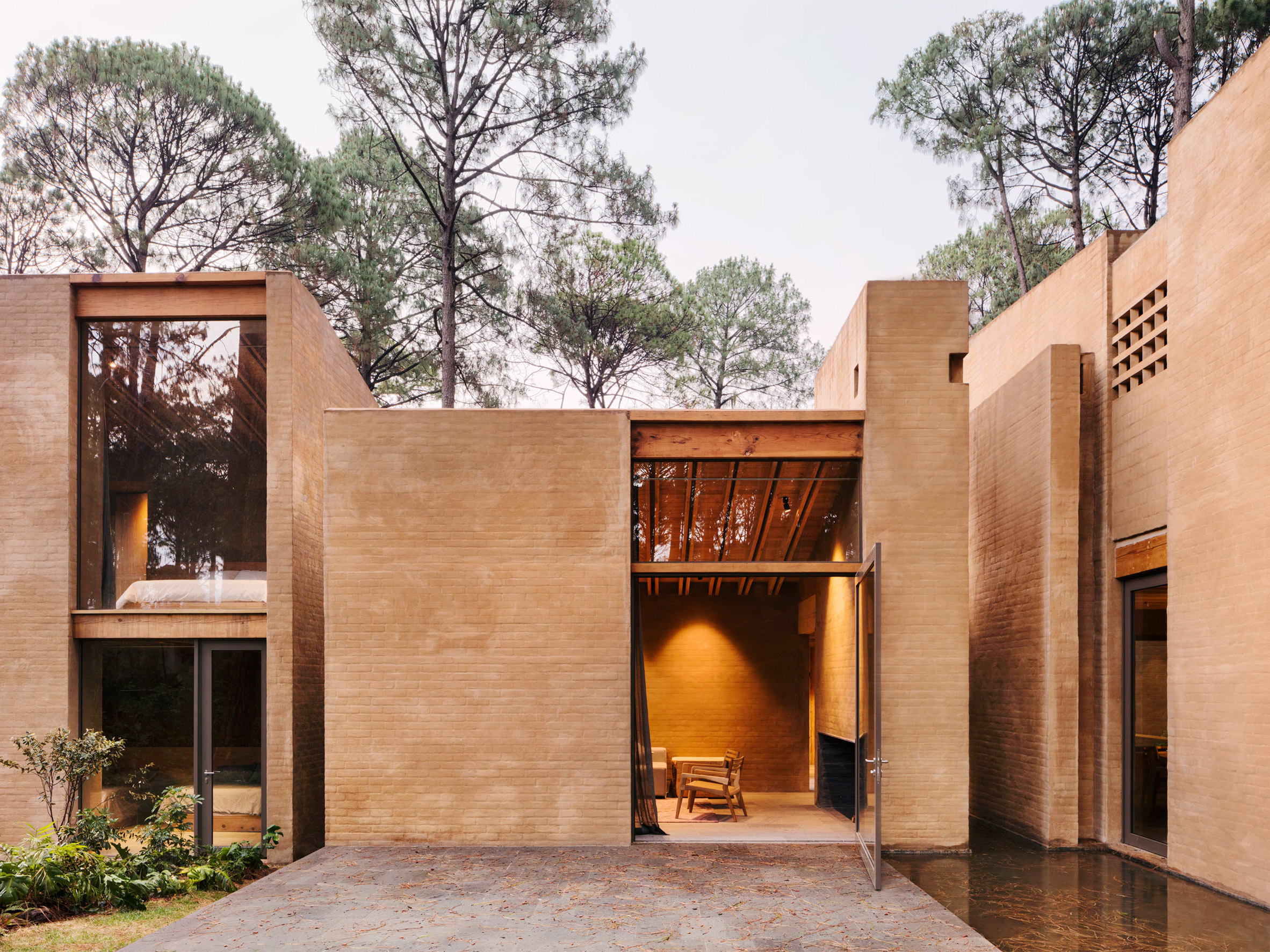 Soil-based render creates pink walls for houses built by Taller Hector Barroso in a Mexican forest