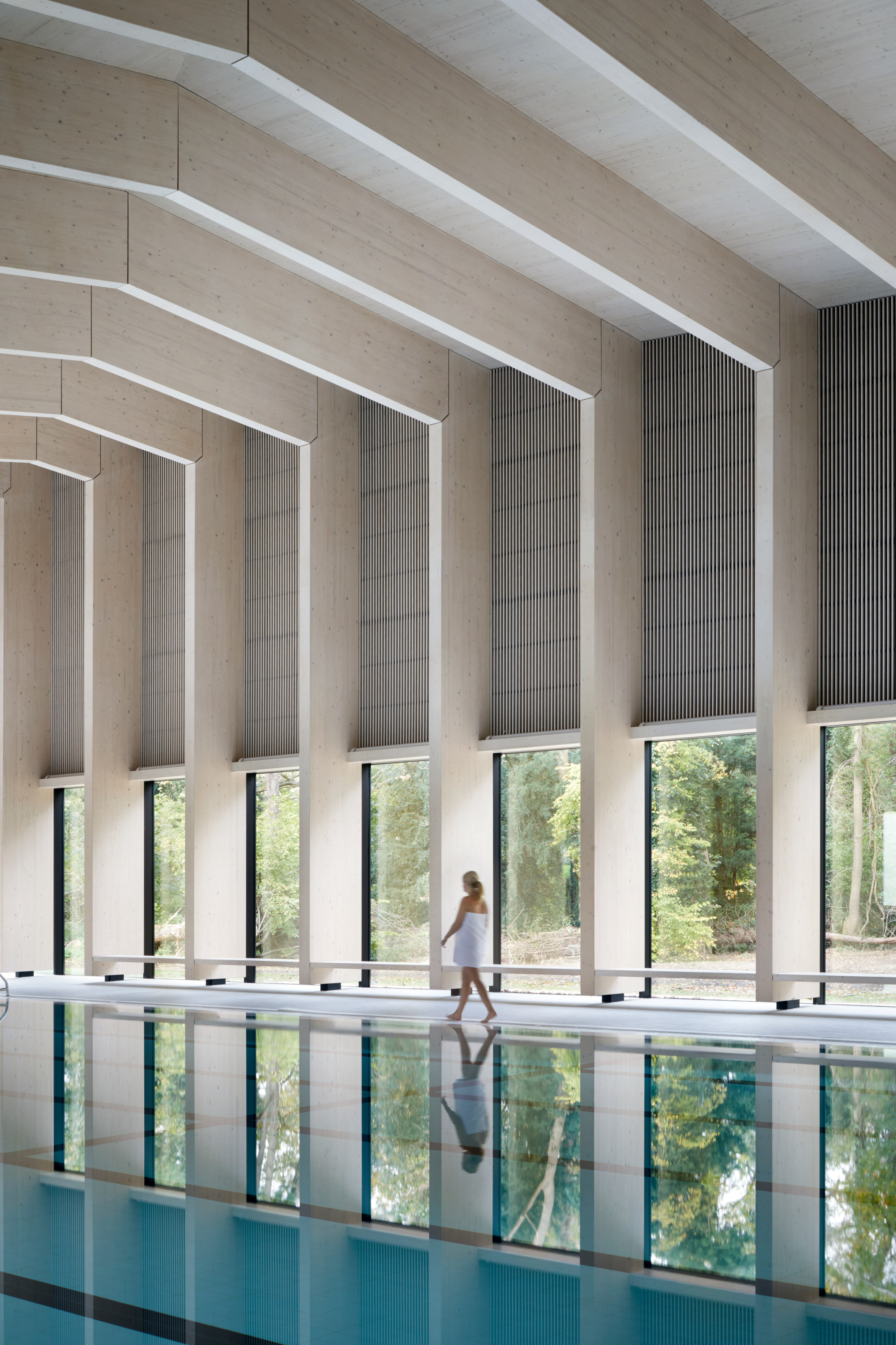 British firm HawkinsBrown has completed a swimming-pool building at a school in Surrey, England, featuring an exposed timber frame that incorporates windows looking out onto the surrounding woodland.