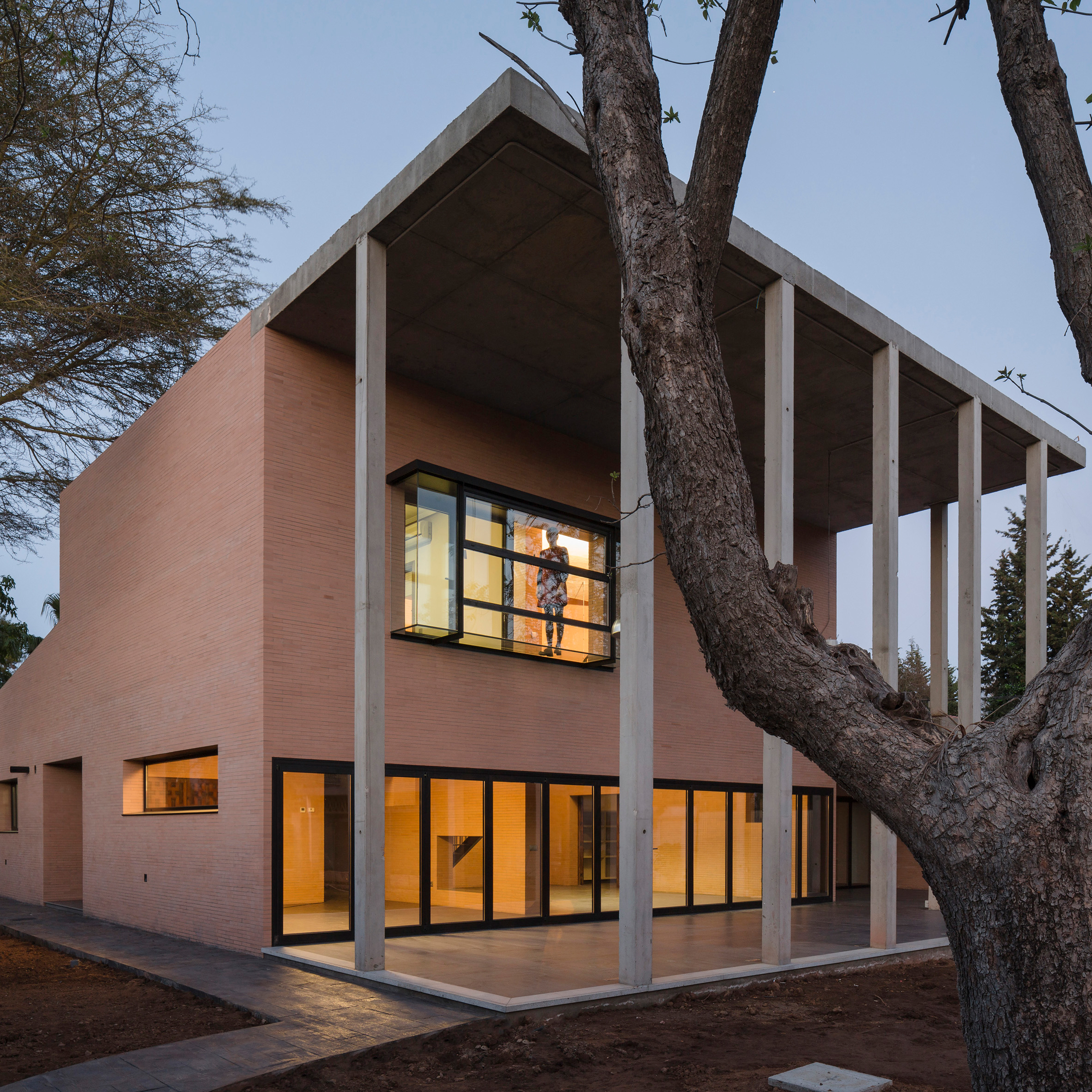 Concrete portico provides sheltered outdoor space for pink brick house in seville