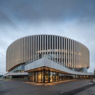 Copenhagen arena by 3XN has an undulating wooden facade that rises up above entrances