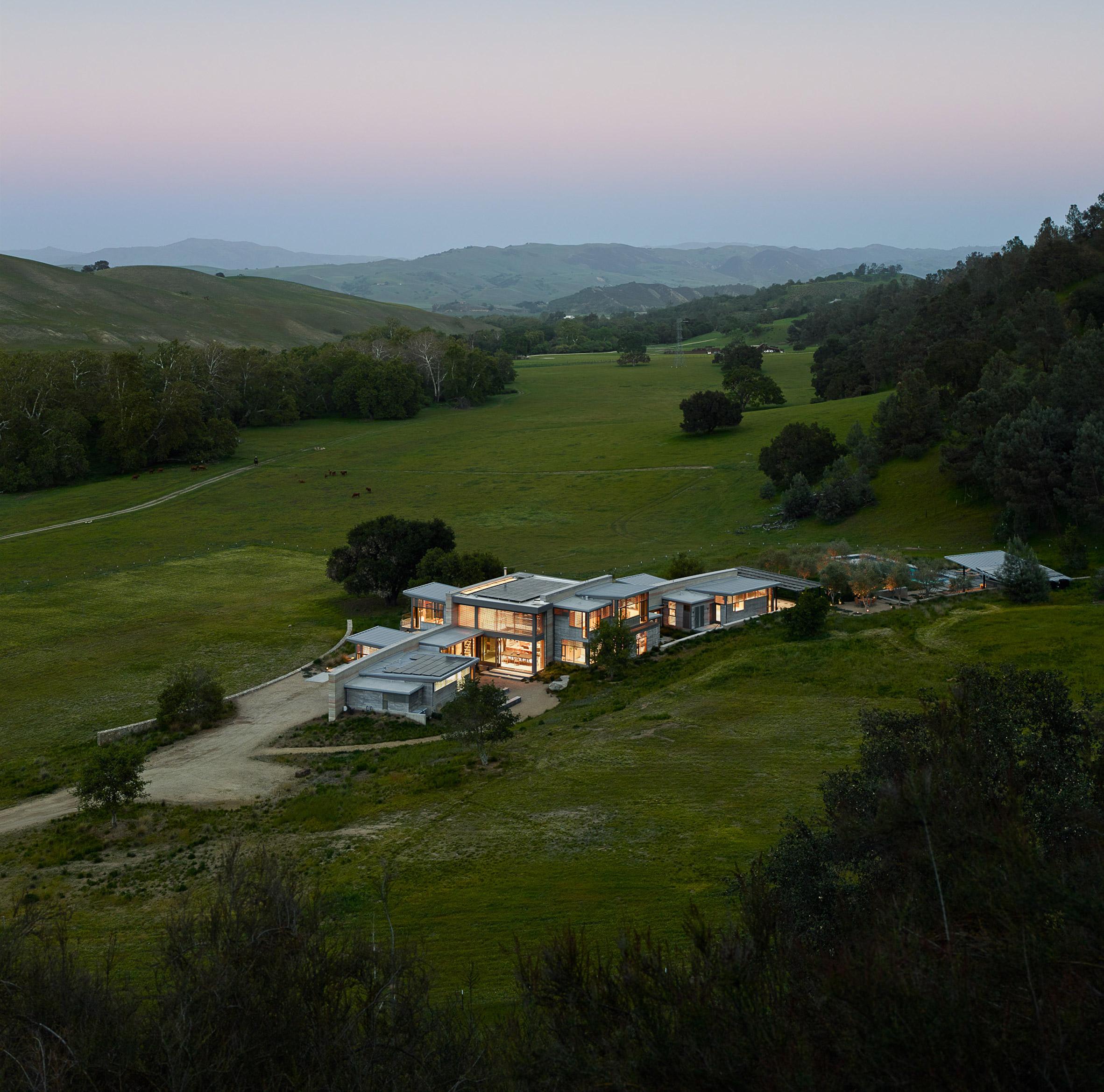 Stripy rammed-earth walls curve through holiday home on Californian walnut farm