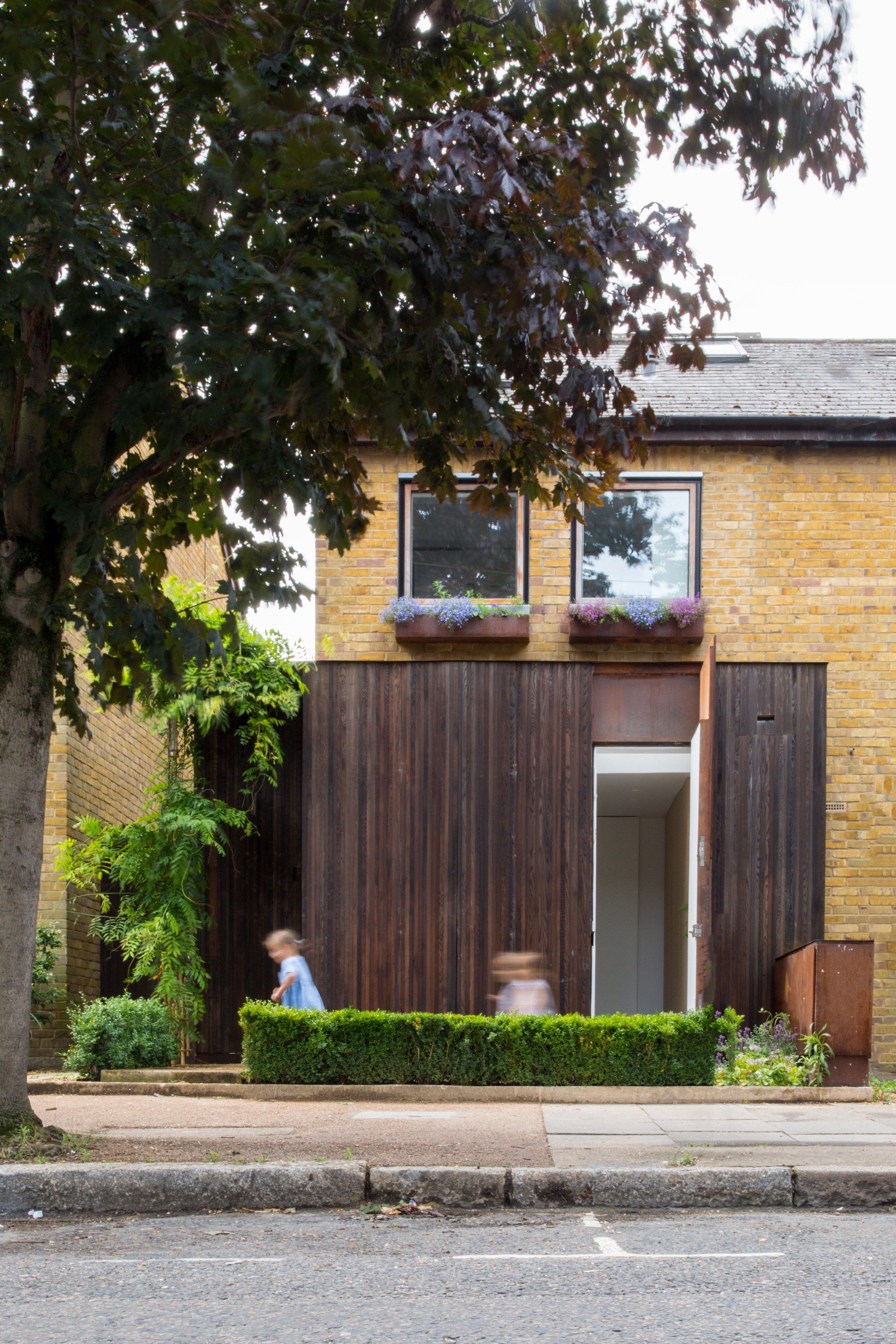 "Checa Romero Architects ""makes the most"" of small brick house by extending in every direction"
