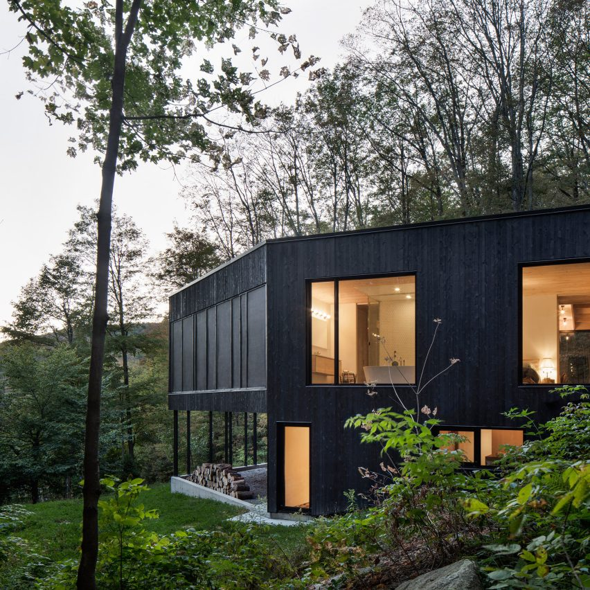 Pilotis support black house on canadian hillside by for Minimalist house quebec