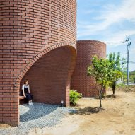 The Vault House by OBBA incorporates hidden gardens behind curving brick walls