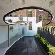 Curved opening frames reflective pool in London house extension by Tonkin Liu