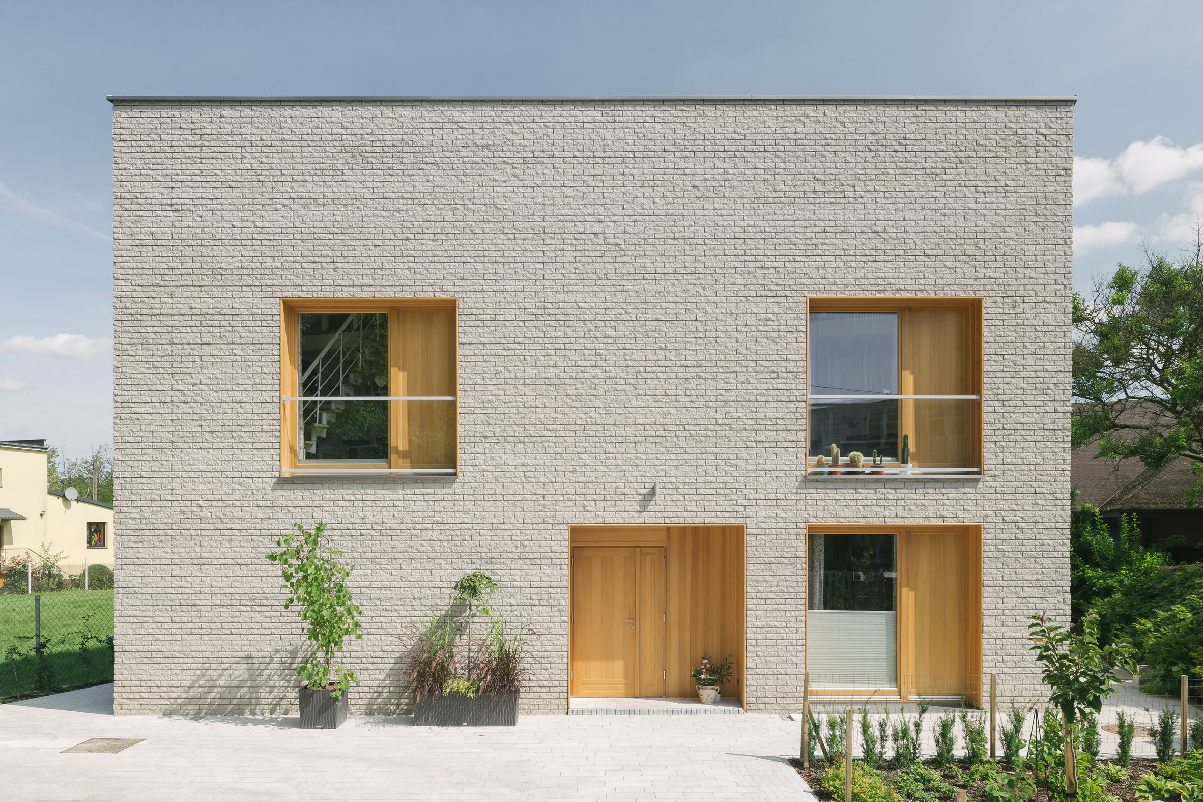 Oak-lined windows contrast pale-brick facades at MFRMGR's house in Warsaw