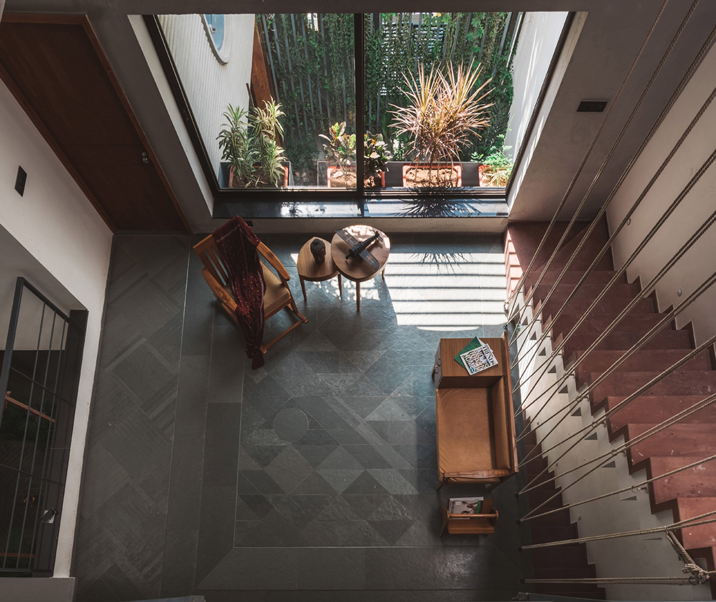 Living spaces at this house in the Indian city of Surat are arranged around a verdant courtyard lined with glass walls that can be retracted to open the interior up to the outdoors