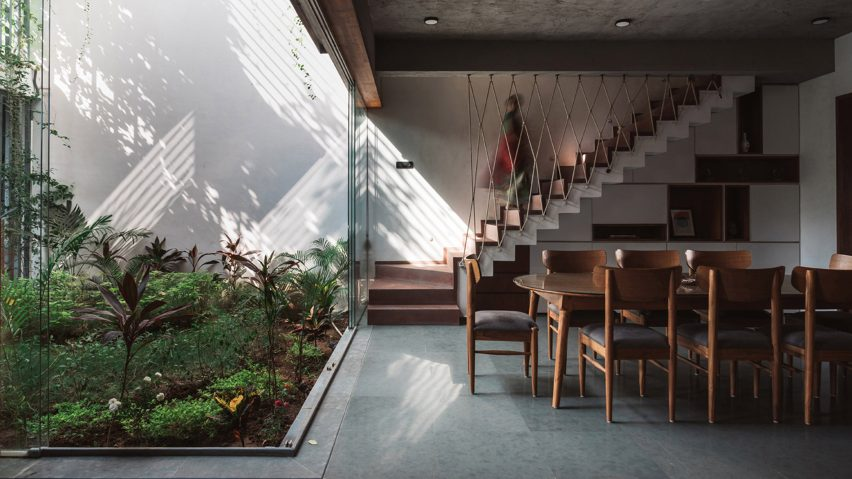 Living spaces at this house in the Indian city of Surat are arranged around a verdant courtyard lined with glass walls that can be retracted to open the interior up to the outdoors.