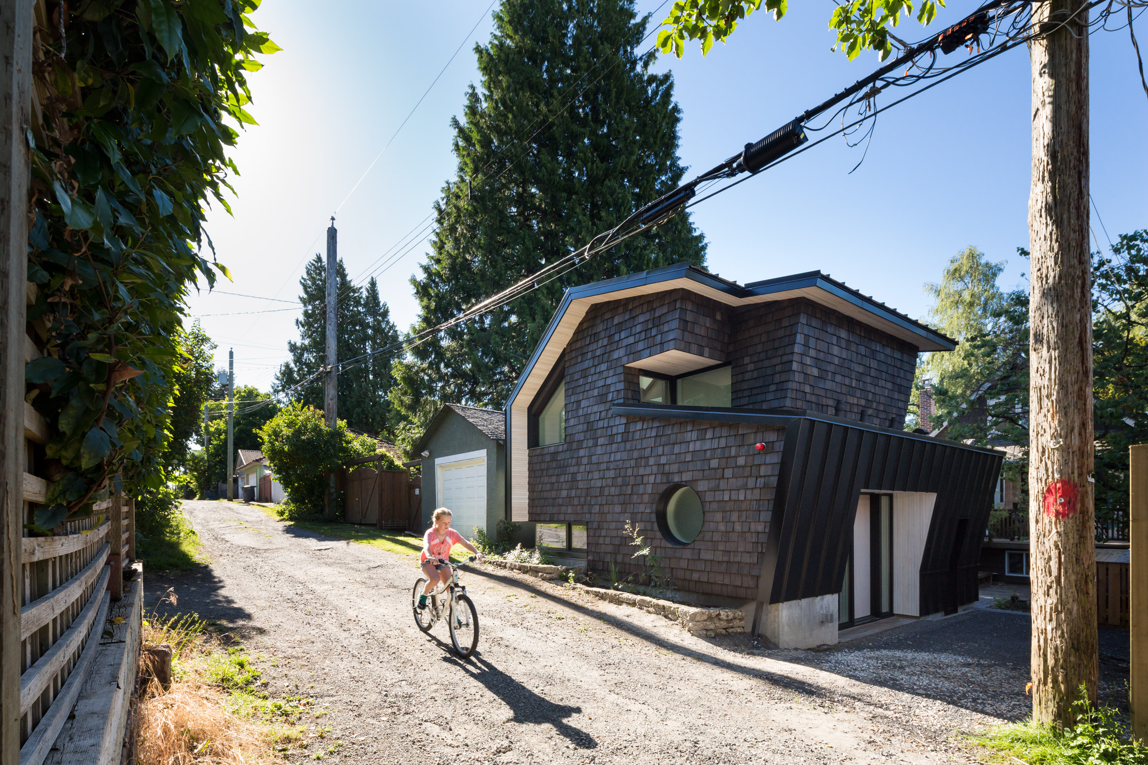 Faceted roof folds over shingle-clad laneway house in Vancouver