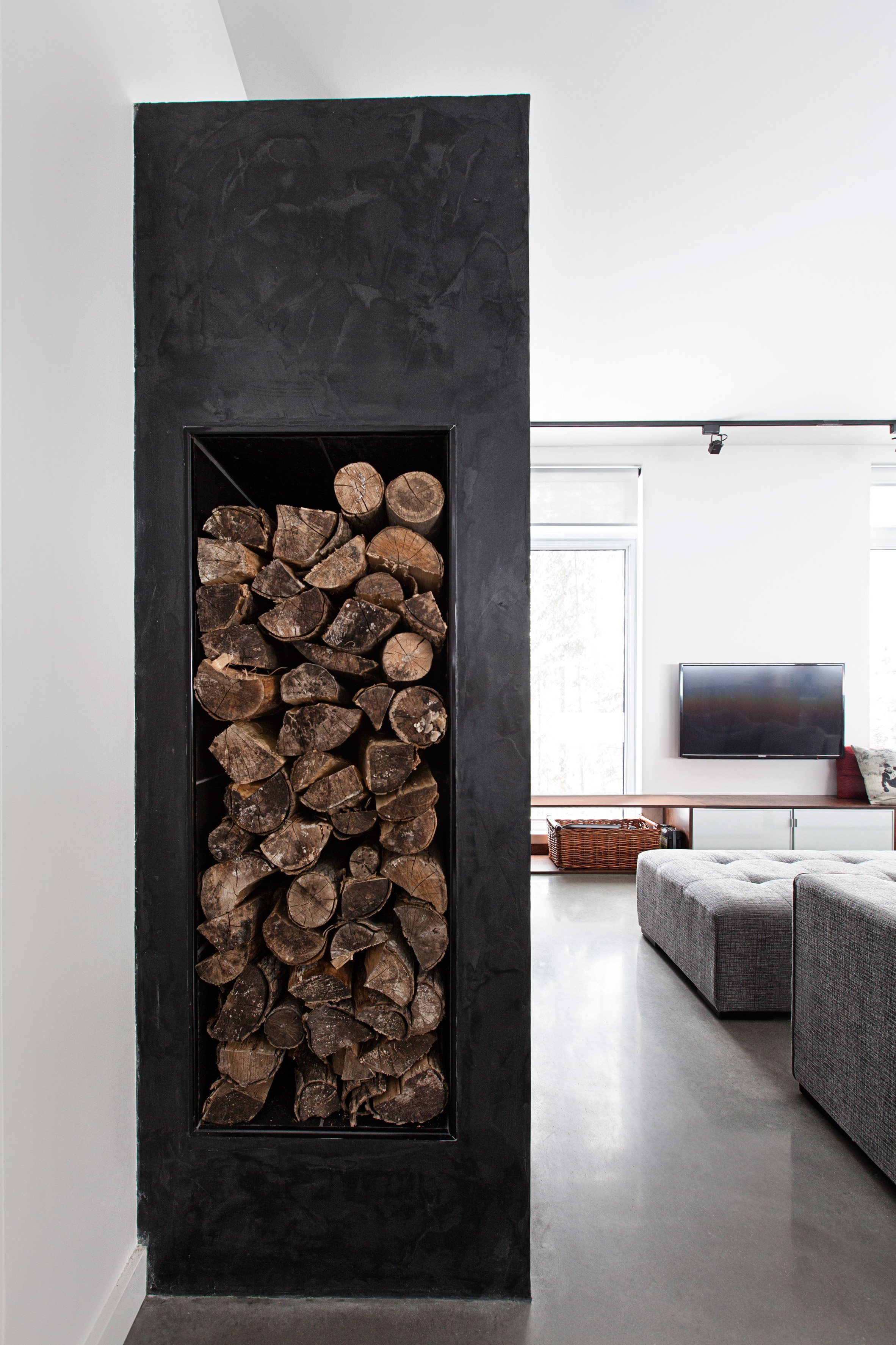 Black concrete fireplace warms Quebec ski lodge by DKA Architects and Kl.tz Design
