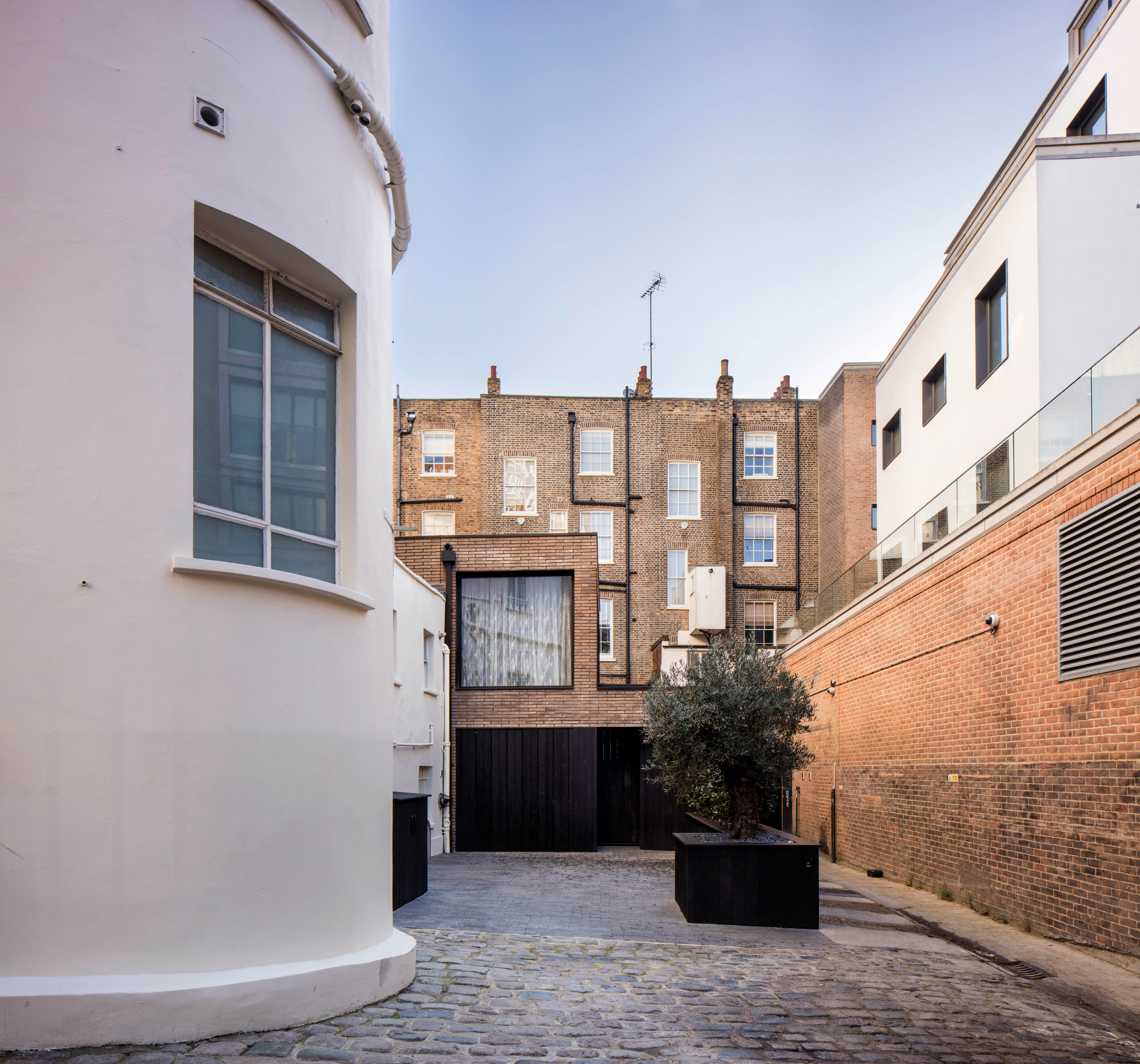 Pivoting louvres conceal windows set into brick facade of mews house by Belsize Architects