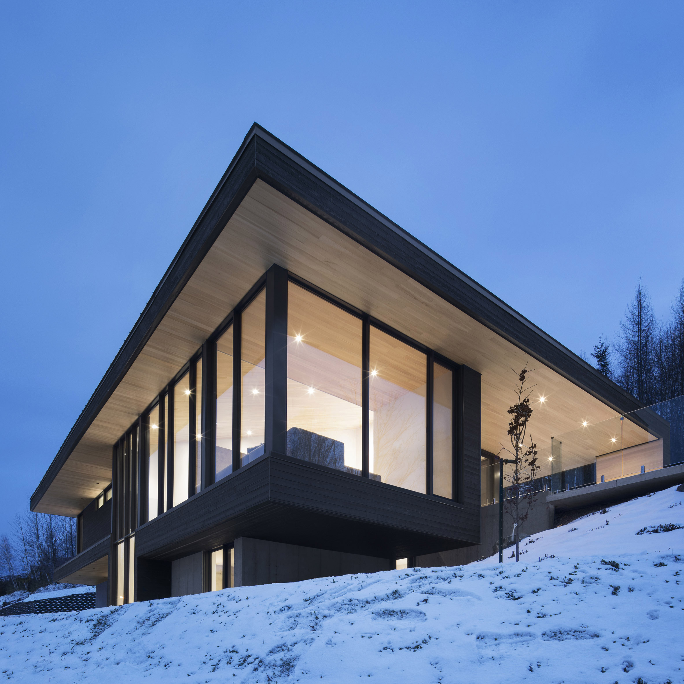 Bourgeois/Lechasseur nestles Quebec home with metal staircase into snowy hillside