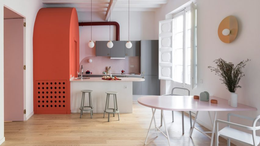 Deep-blue cabinetry and coral-pink arches redefine Barcelona apartment
